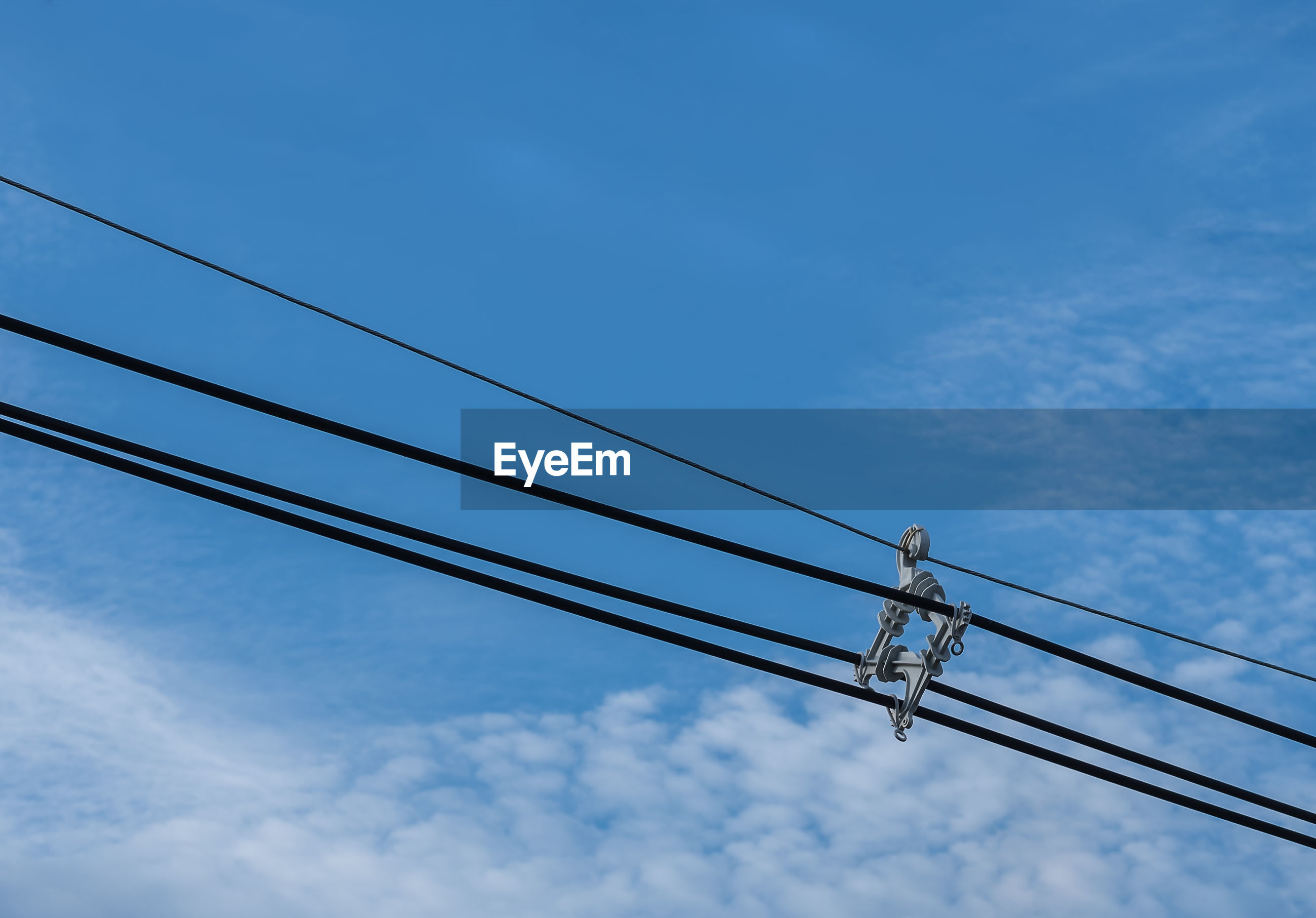 Low angle view of electricity cable against blue sky