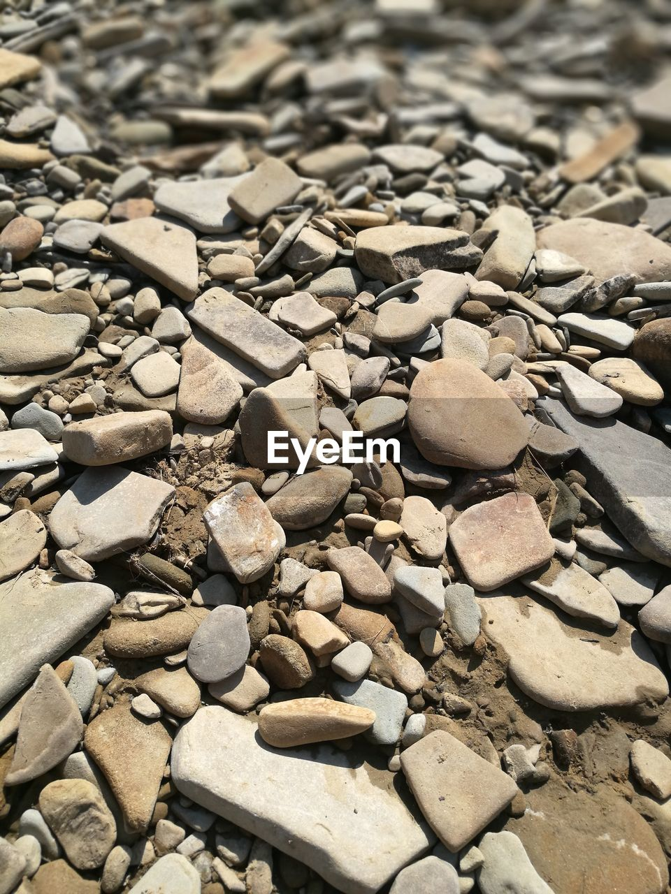 solid, full frame, large group of objects, rock, backgrounds, stone - object, abundance, no people, day, stone, nature, pebble, close-up, textured, sunlight, high angle view, rock - object, outdoors, beach, rough, gravel