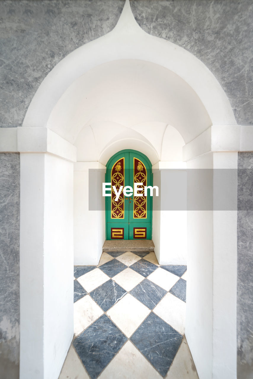 arch, architecture, built structure, building, no people, entrance, door, day, indoors, religion, arcade, sunlight, flooring, corridor, place of worship, architectural column, belief, nature, tiled floor