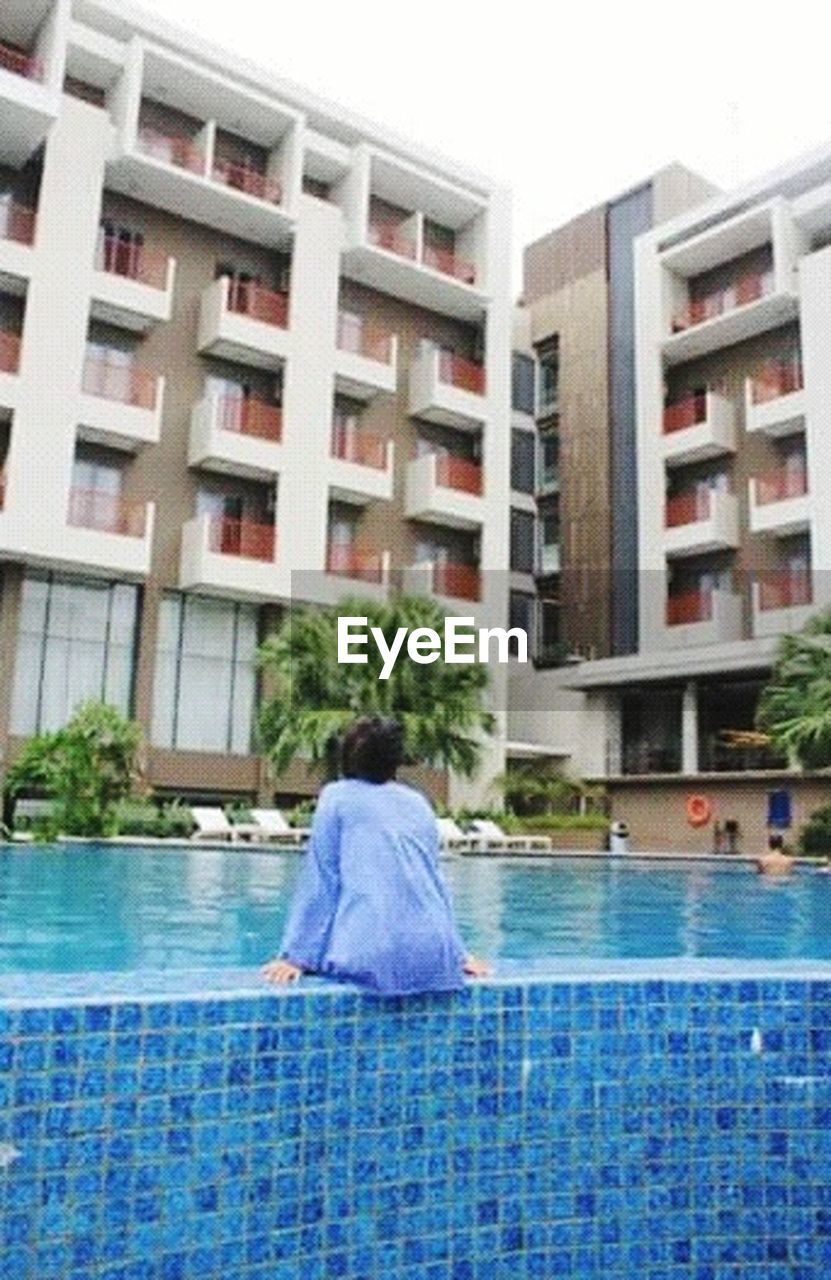 swimming pool, water, building exterior, architecture, one person, rear view, day, outdoors, people, window, built structure, luxury, vacations, health spa, luxury hotel, adults only, only women, city, swimming, adult, young adult