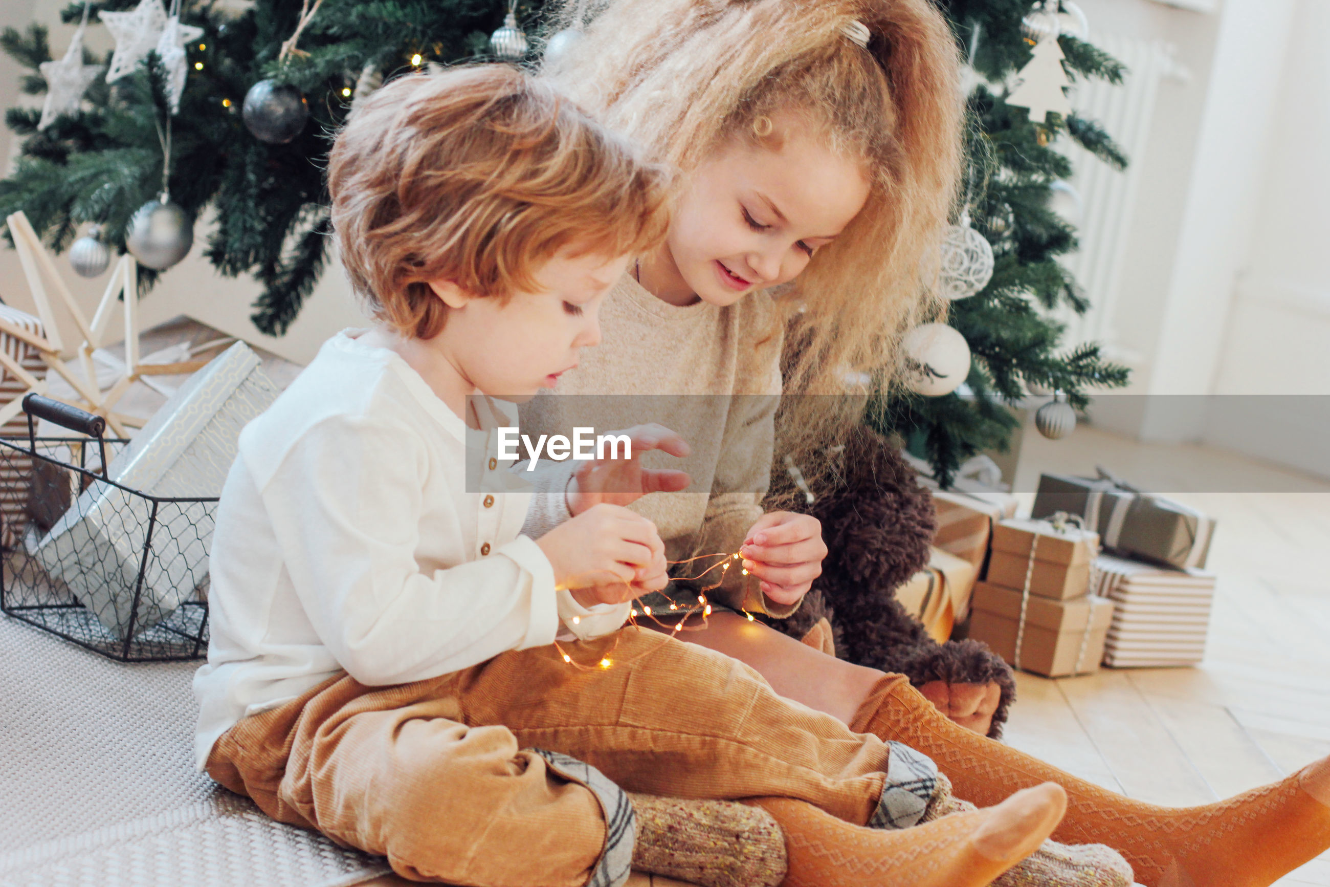 Girl with brother sitting by christmas tree at home