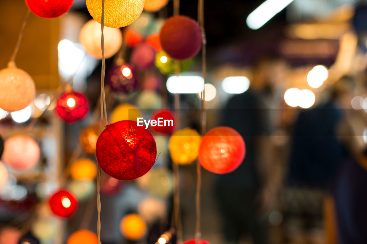 illuminated, focus on foreground, night, close-up, lighting equipment, red, hanging, decoration, lens flare, multi colored, no people, glowing, celebration, outdoors, electricity, light - natural phenomenon, shape, defocused, selective focus