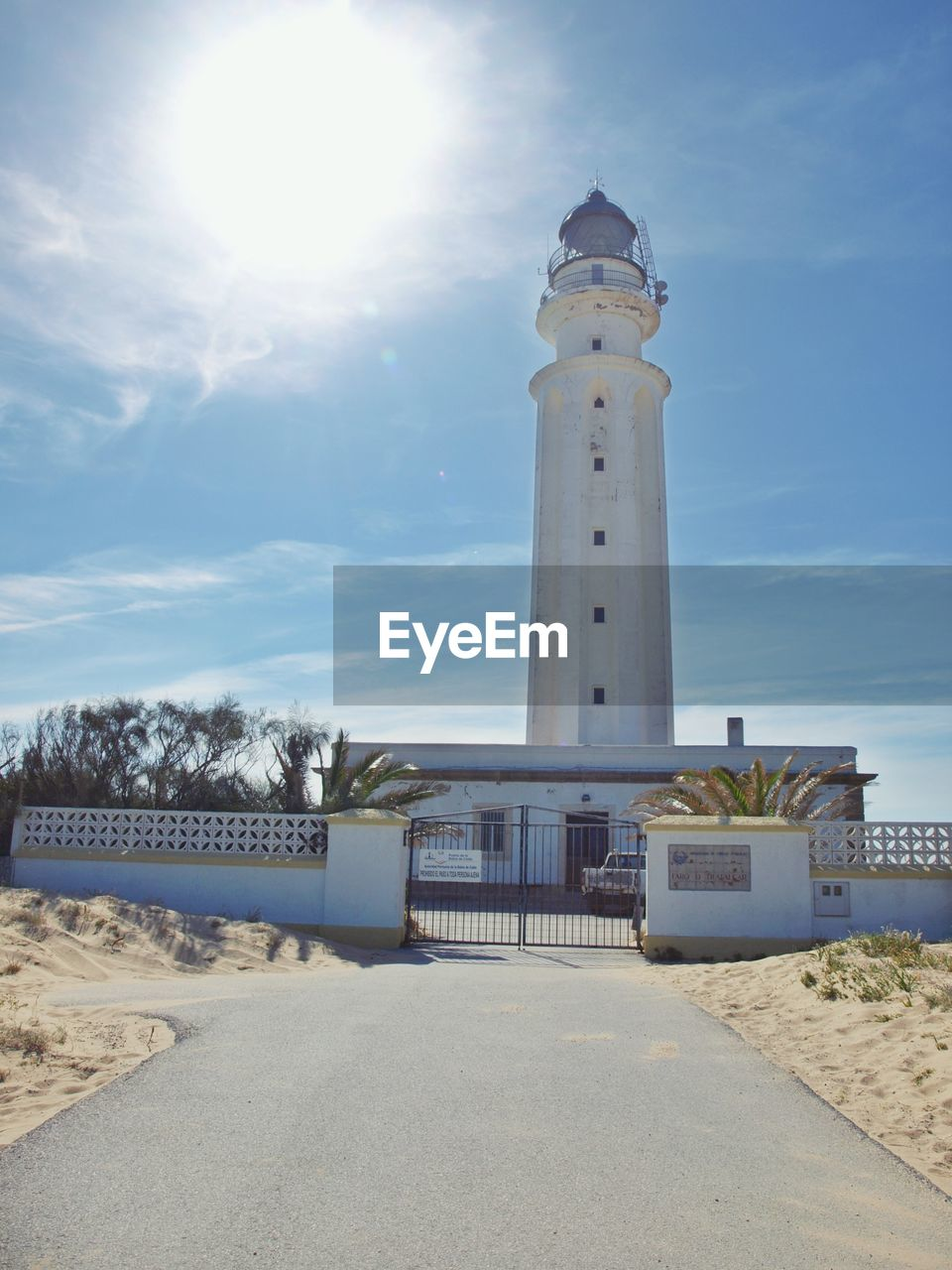 sky, built structure, architecture, tower, nature, lighthouse, sunlight, land, cloud - sky, building exterior, guidance, day, beach, building, security, protection, no people, direction, safety, low angle view, outdoors