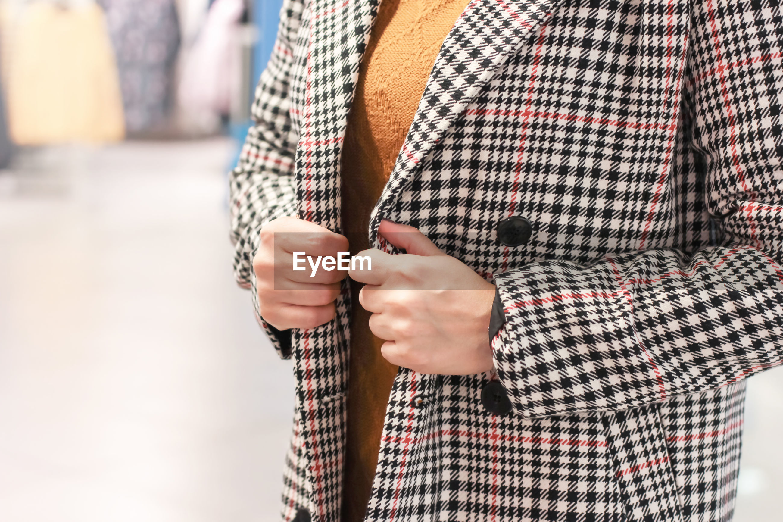 Close-up midsection of woman wearing check patterned overcoat