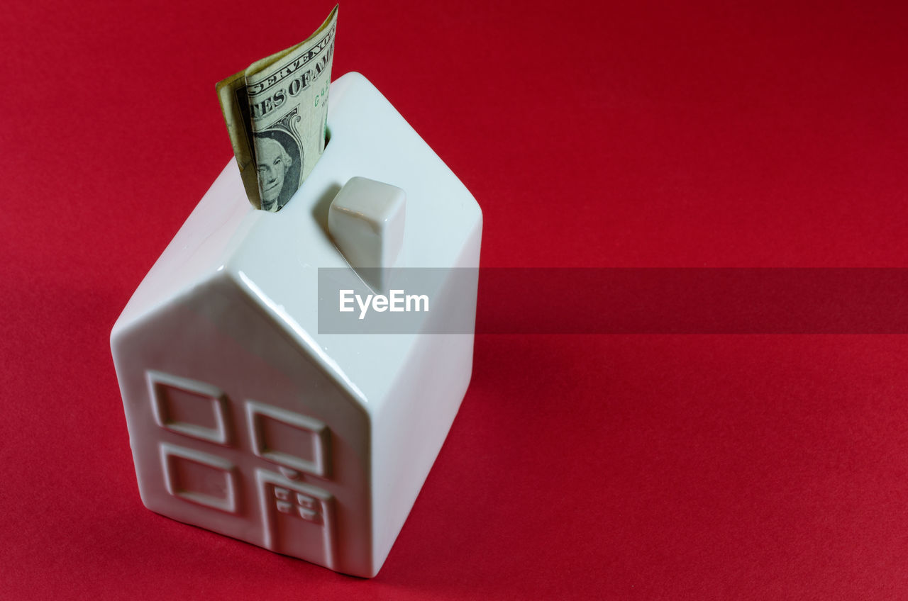 High Angle View Of Model Home With Paper Currency On Red Background
