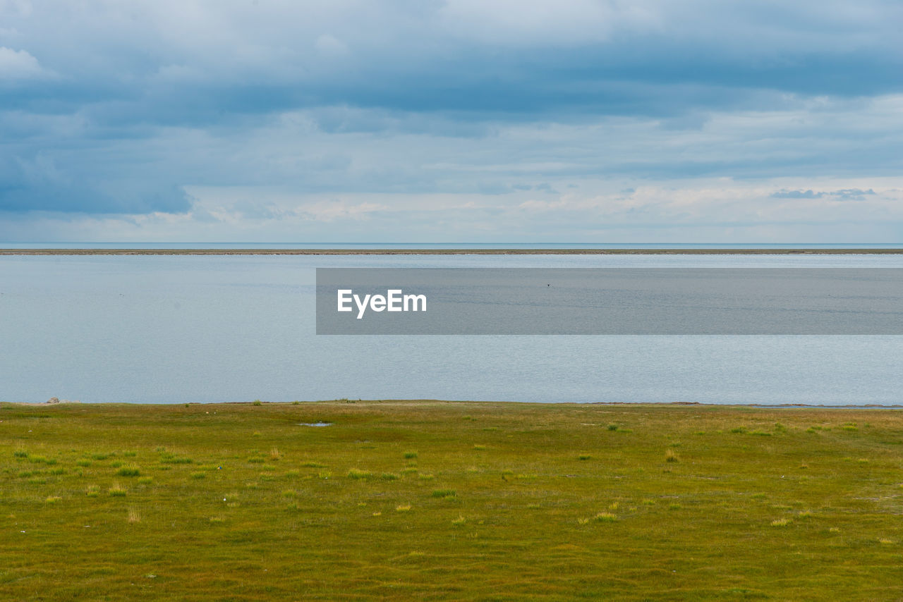 sky, cloud - sky, scenics - nature, beauty in nature, tranquil scene, tranquility, water, land, no people, horizon, day, environment, nature, grass, sea, landscape, non-urban scene, green color, outdoors