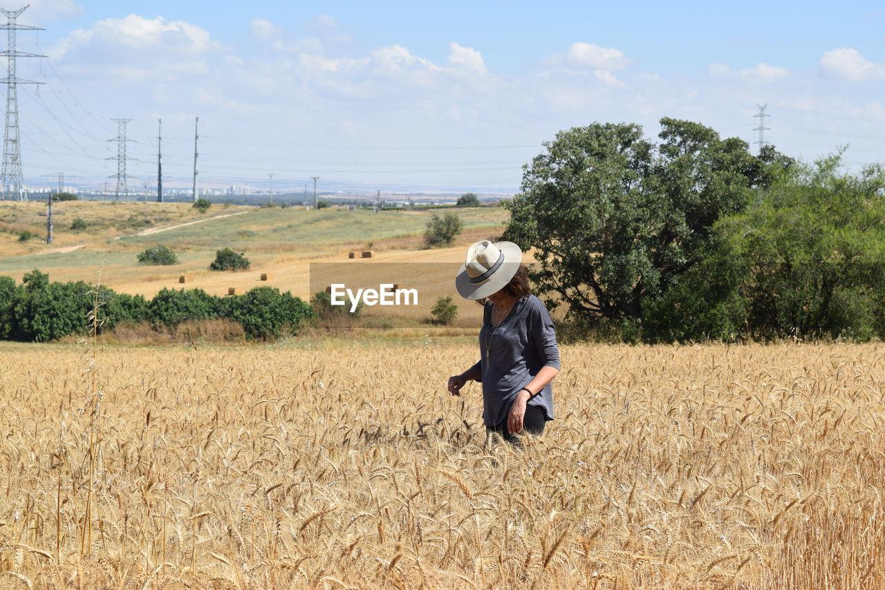 Woman in field against sky