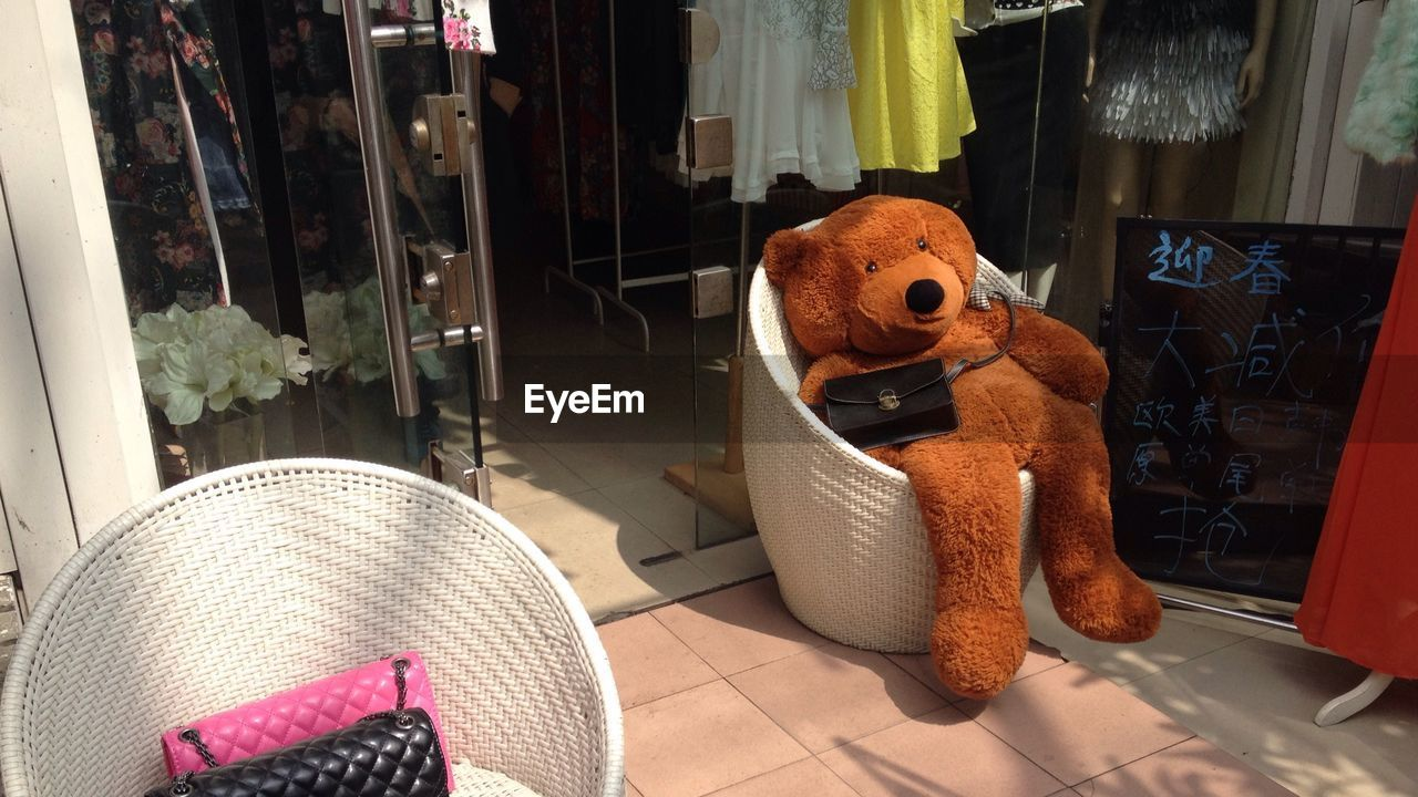 High Angle View Of Teddy Bear On Chair Outside Shop