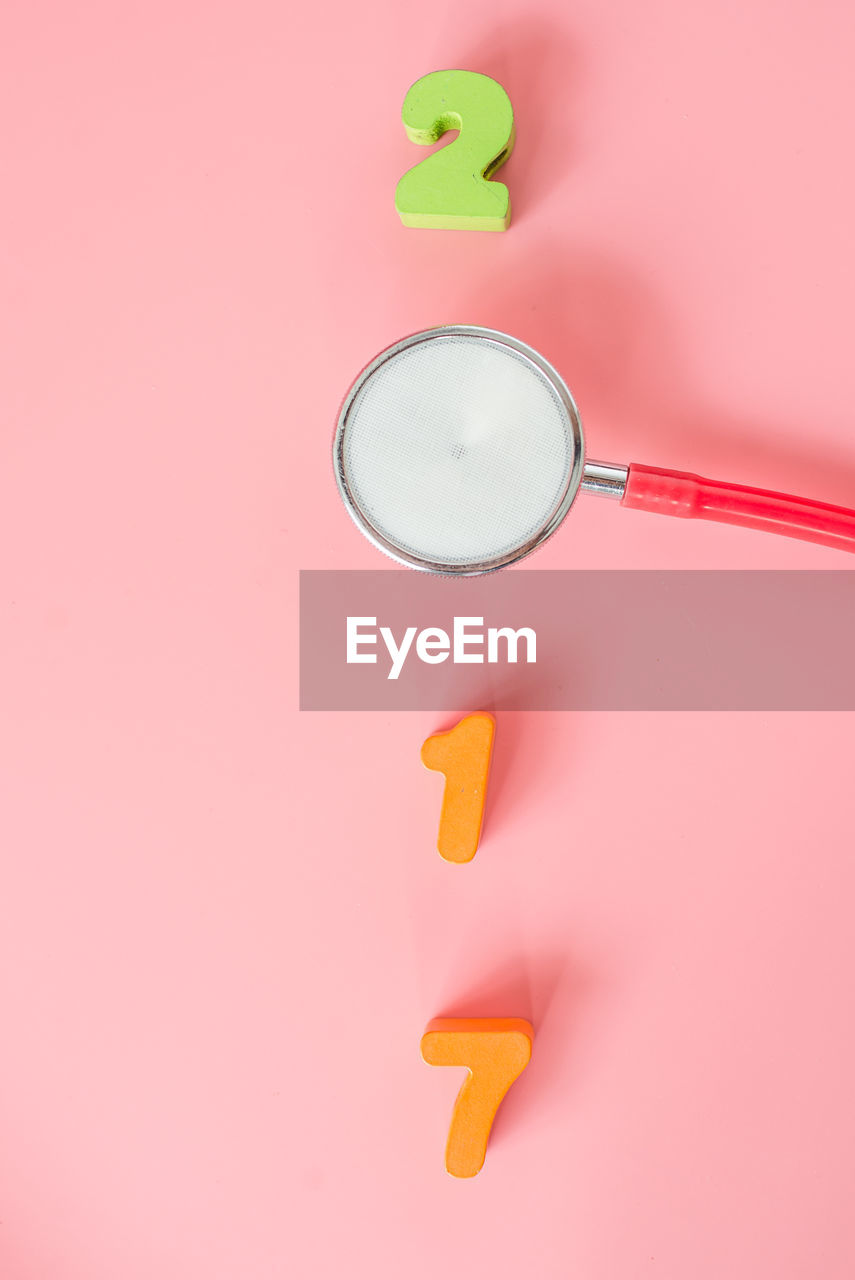 Close-up of stethoscope and numbers against pink background