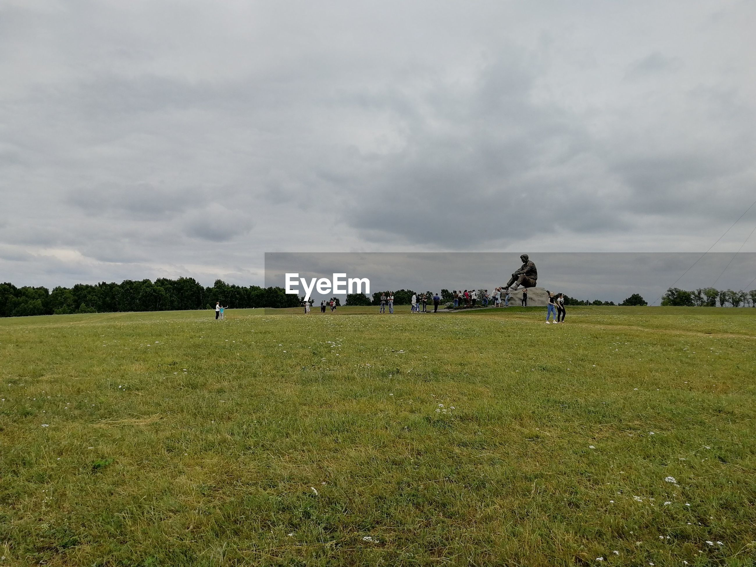 People on grassy field against cloudy sky at park