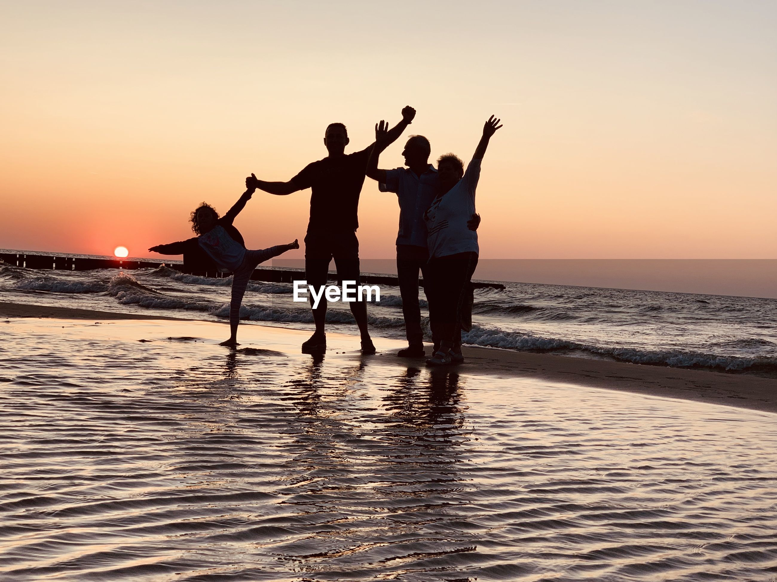 Cheerful people standing at beach during sunset