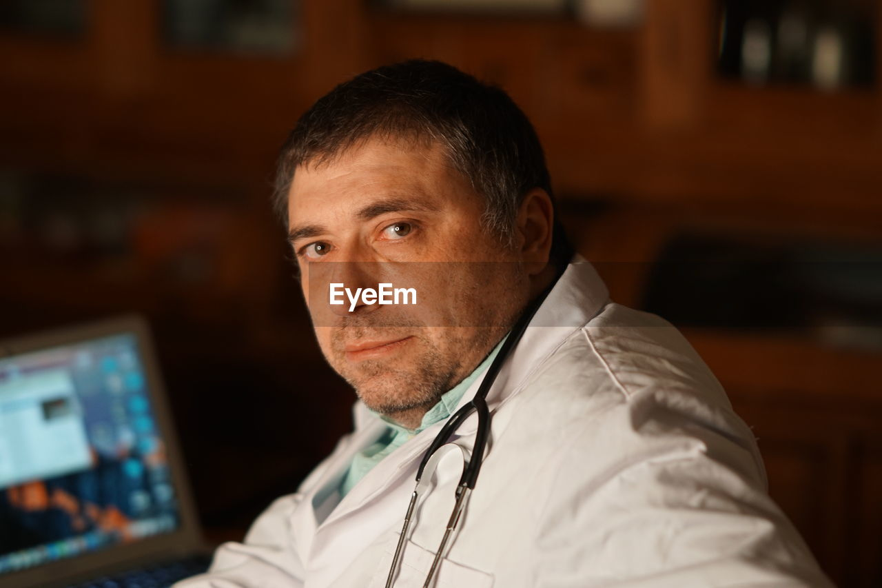 Portrait Of Mature Doctor Sitting In Hospital