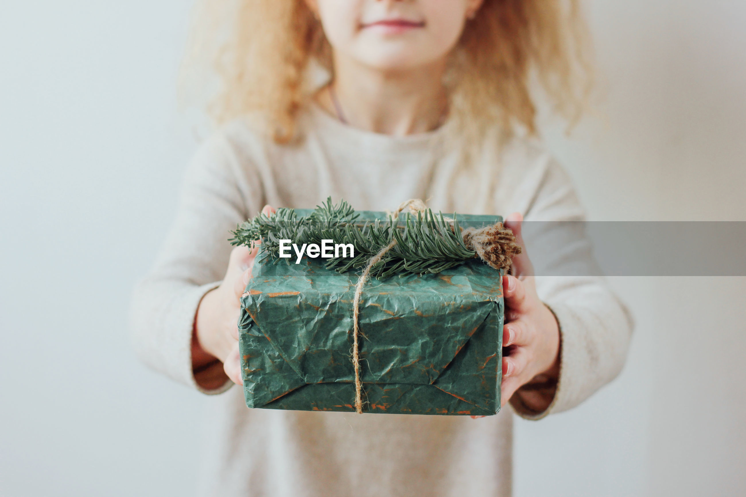Midsection of girl holding christmas present against wall