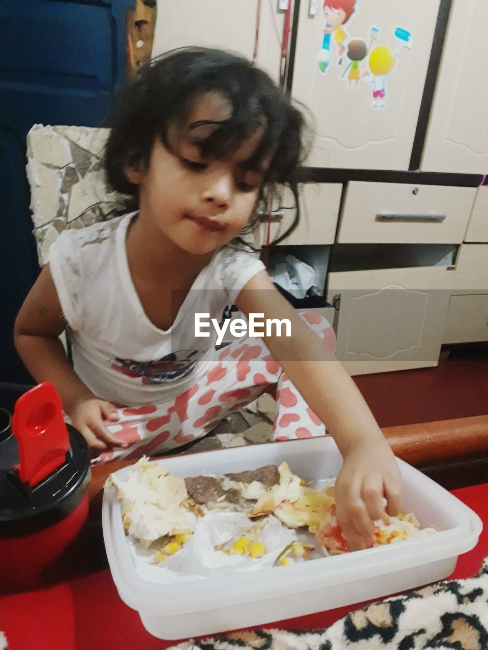 child, childhood, one person, food and drink, food, real people, girls, front view, females, women, lifestyles, indoors, casual clothing, table, leisure activity, home interior, cute, holding, innocence, preparing food