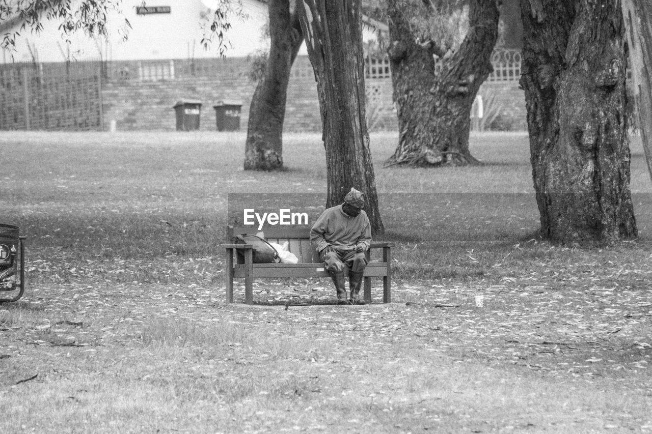 Full Length Of Man Sitting On Bench At Park