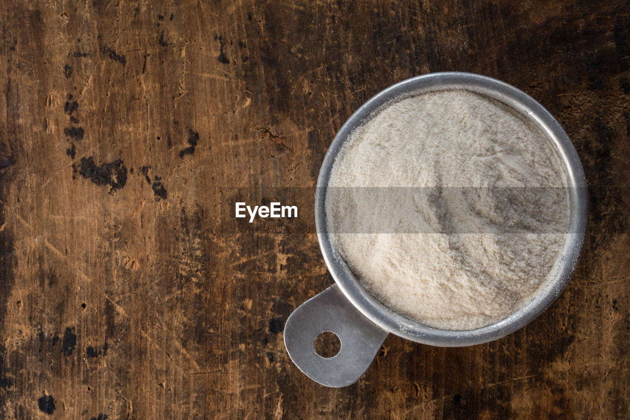 Directly above shot of xanthan gum in measuring cup on wooden table
