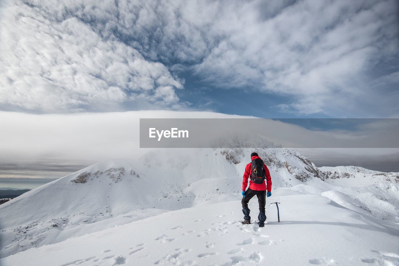winter, snow, cold temperature, cloud - sky, sky, leisure activity, beauty in nature, rear view, mountain, scenics - nature, real people, full length, lifestyles, white color, holiday, sport, vacations, trip, nature, warm clothing, outdoors, snowcapped mountain