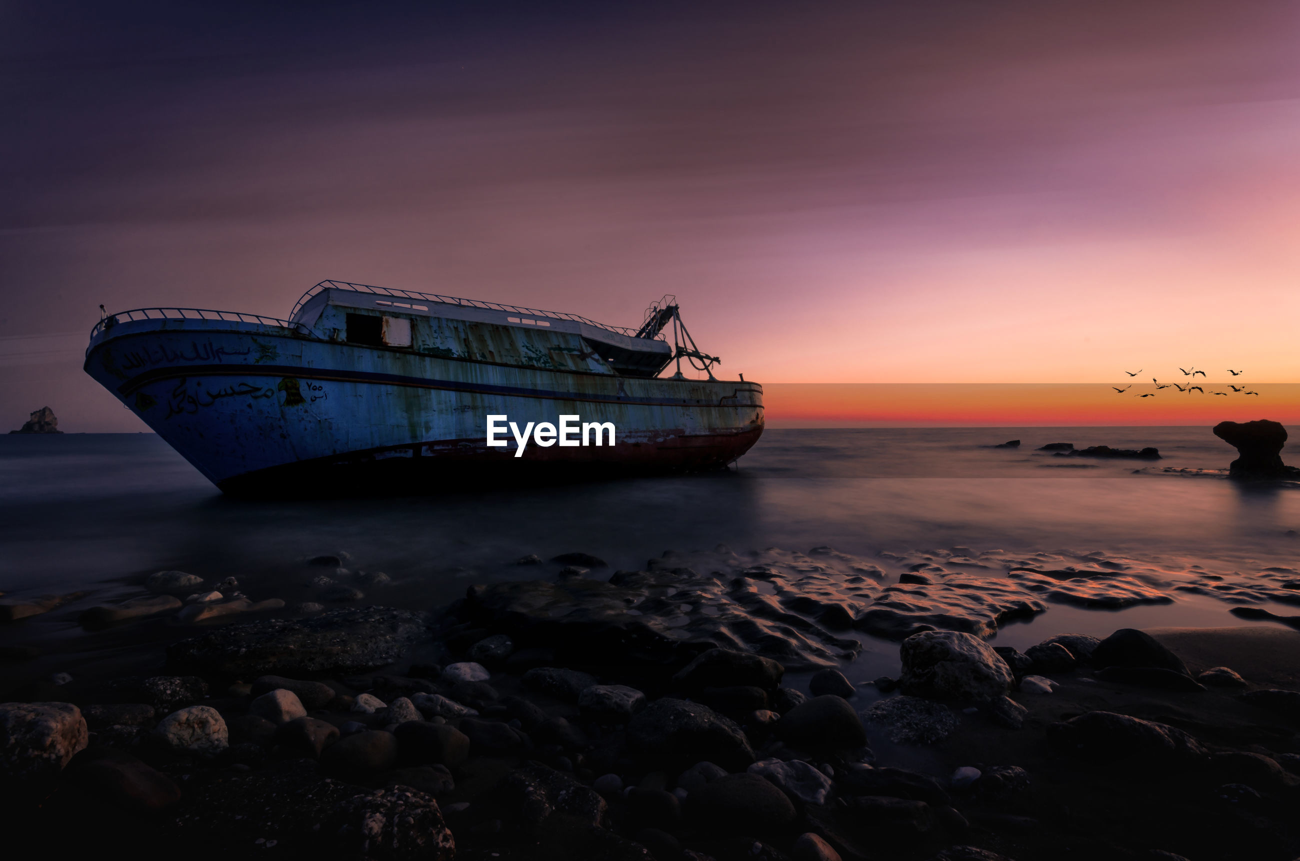 Scenic view of old boat at sea during sunset