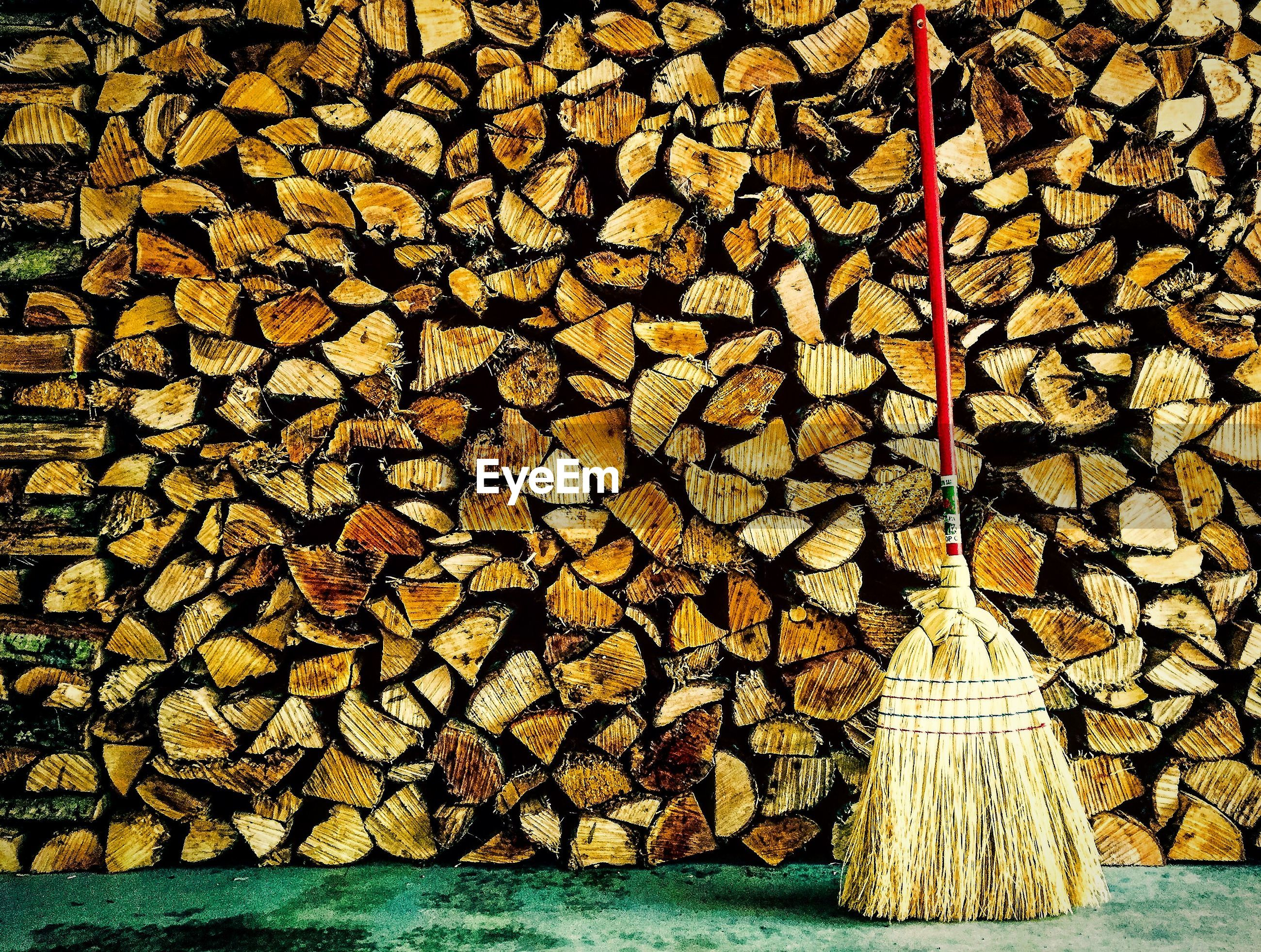 Broom against stacked logs