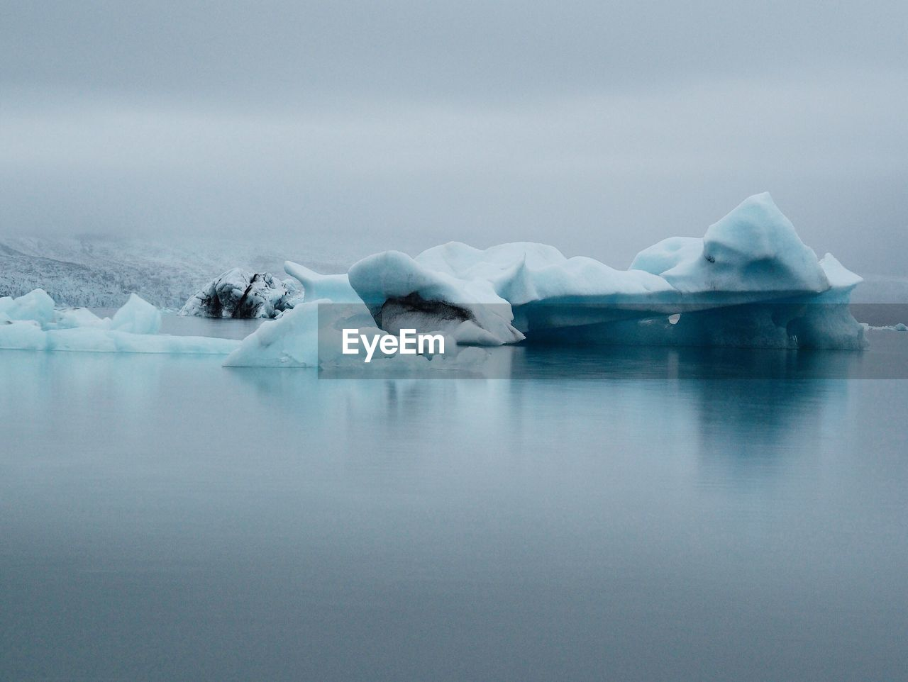 Scenic View Of Iceberg On Foggy Lake