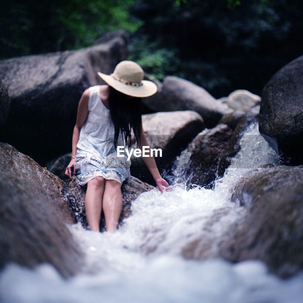 Woman Sitting On Rock In Stream