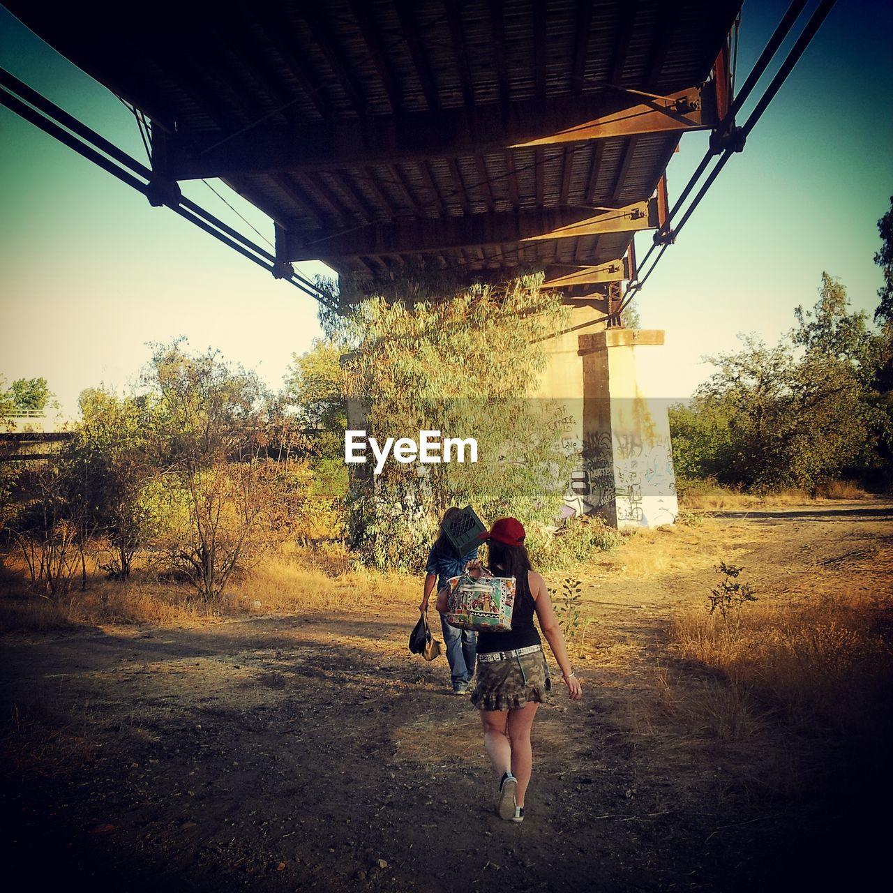 Rear view of man and woman walking under bridge