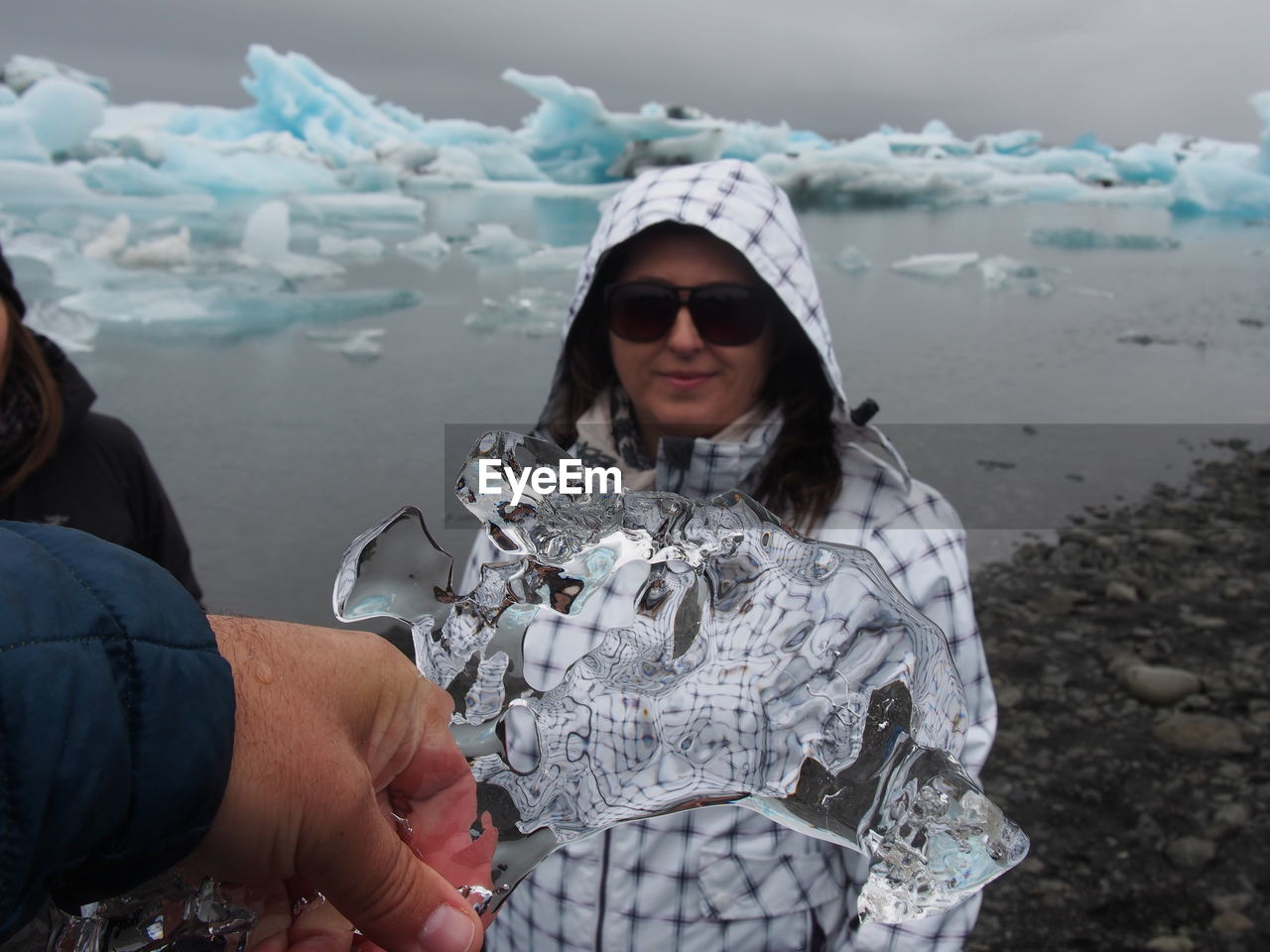 Cropped Hand Of Man Holding Icicle Against Woman At Beach