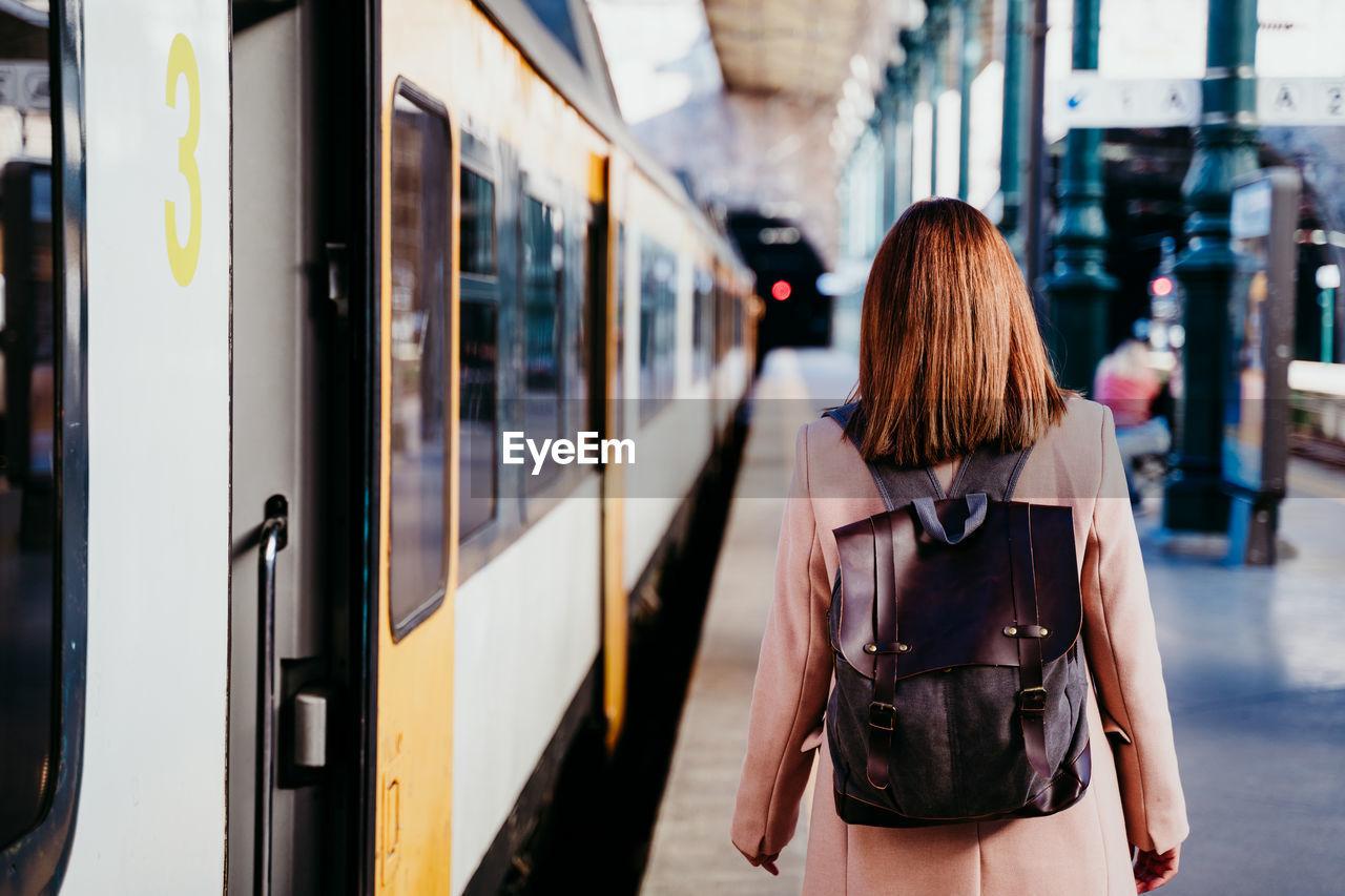 Woman walking by train on railroad station platform