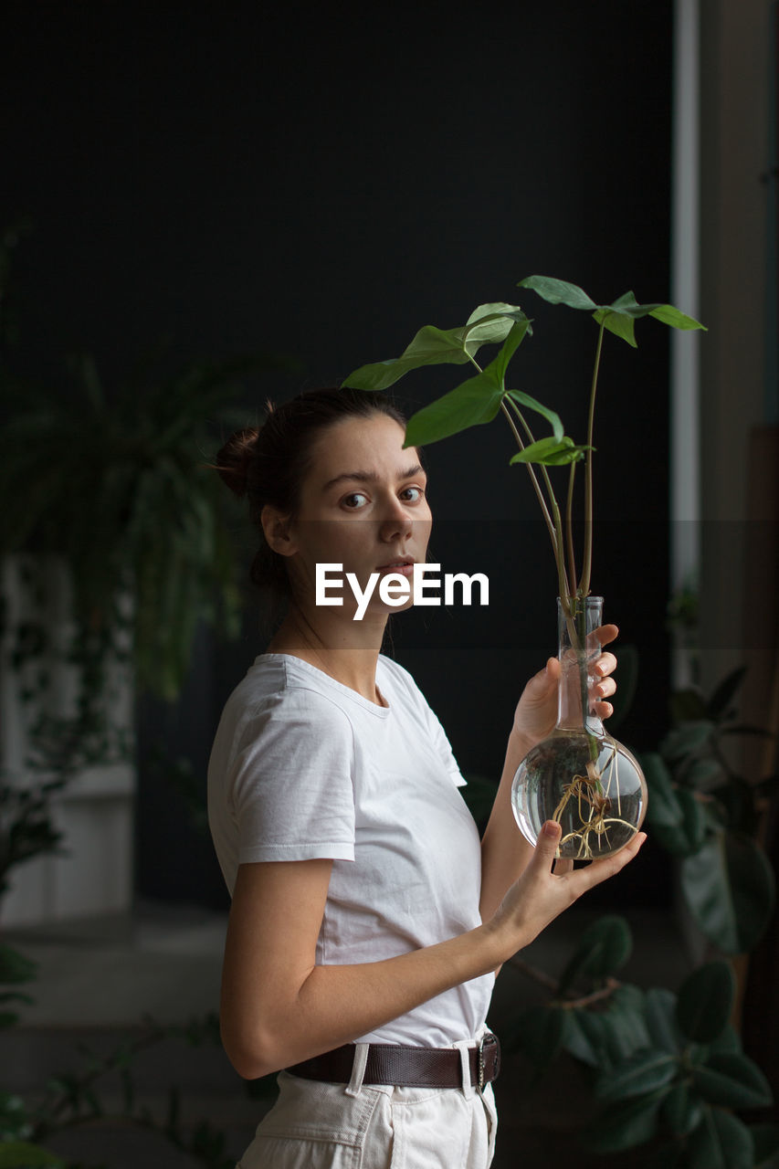 PORTRAIT OF WOMAN HOLDING POTTED PLANT AT HOME