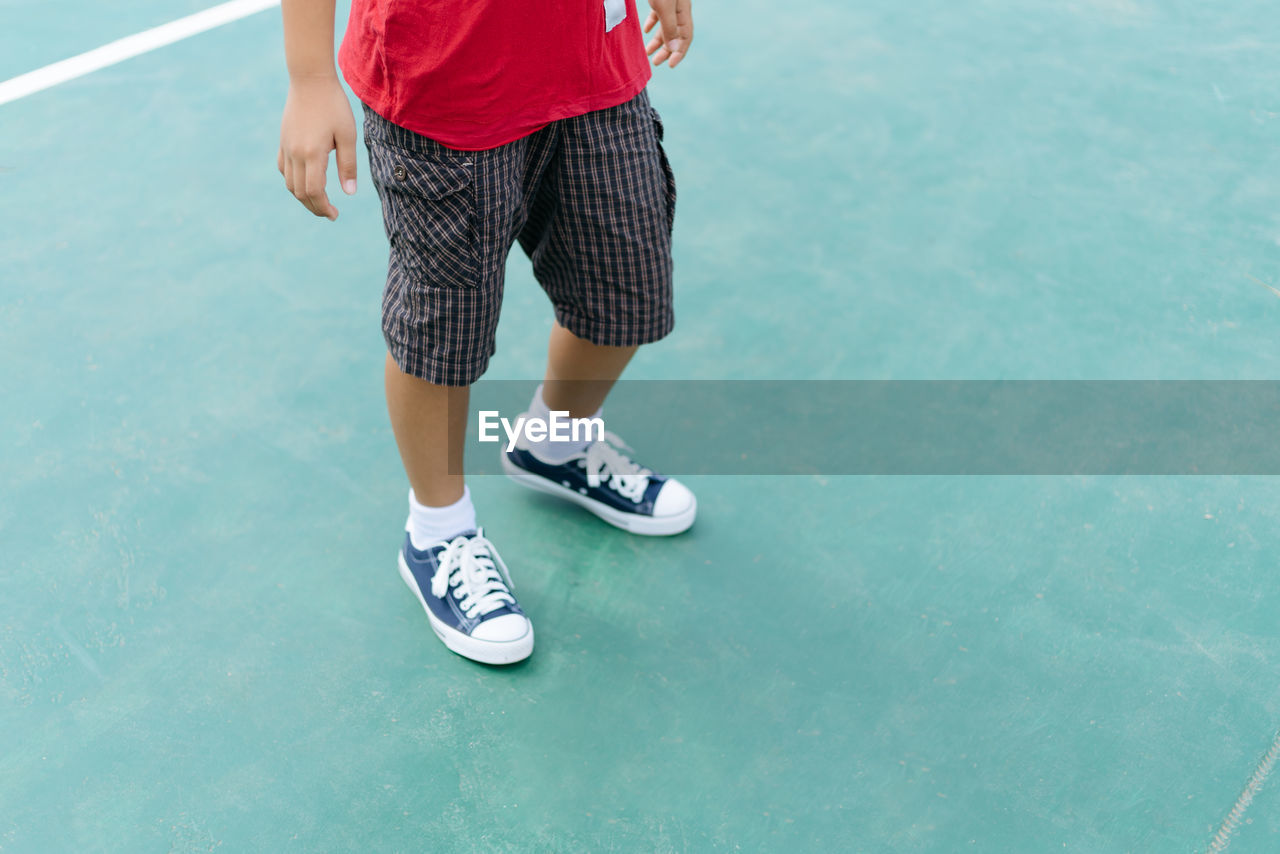 Low section of man standing at tennis court