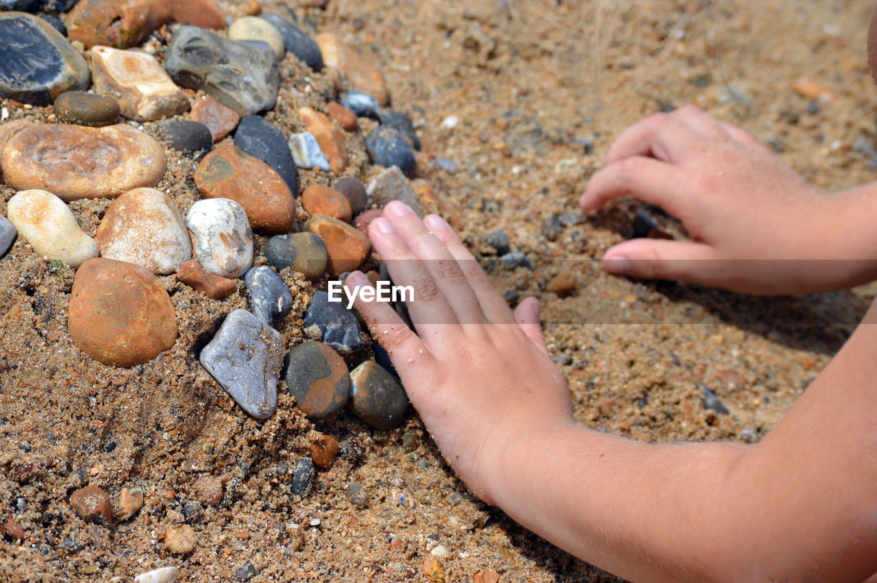 CLOSE-UP OF HAND HOLDING PEBBLES ON ROCK