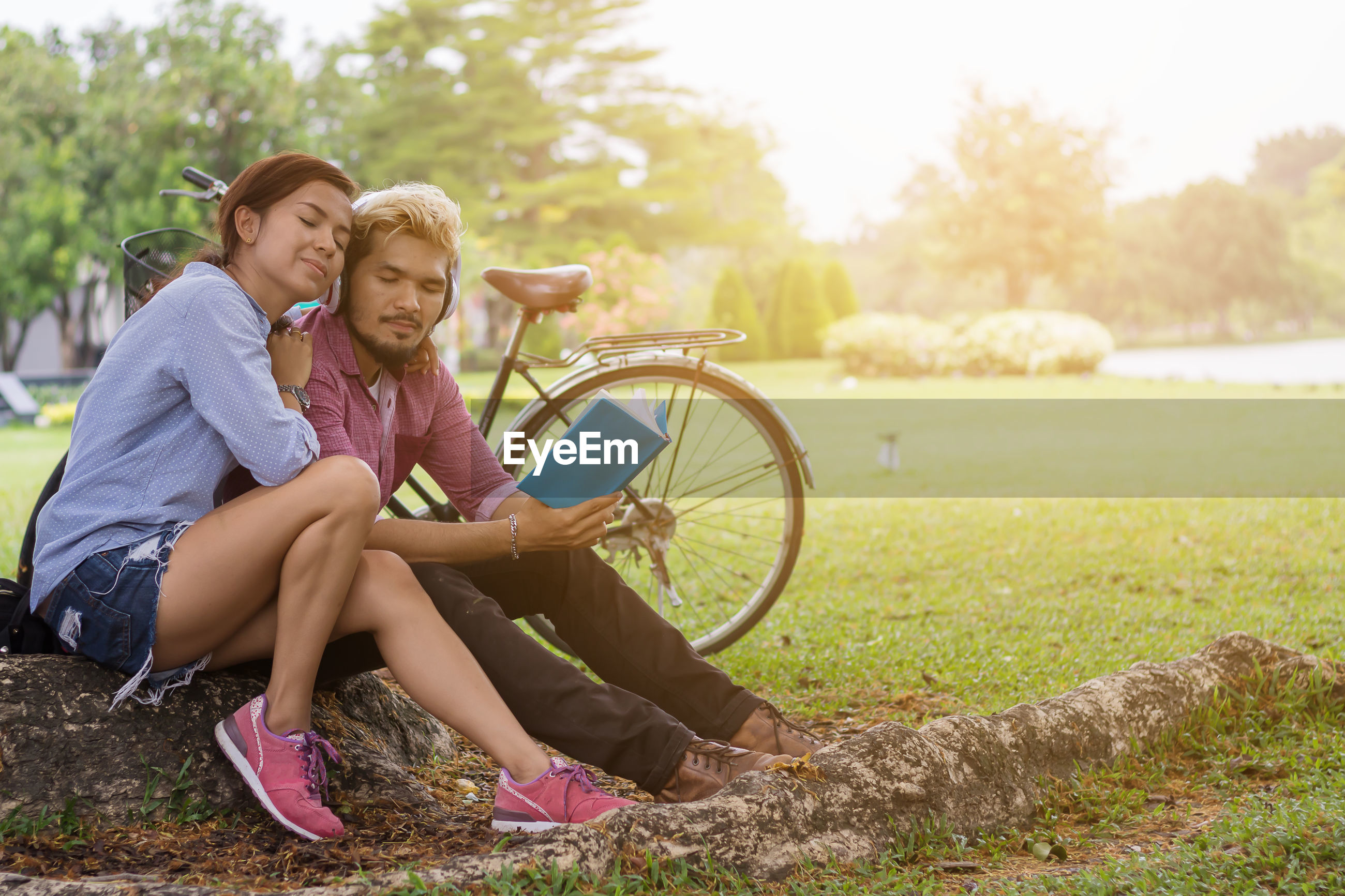 Couple sitting on grass listening to music