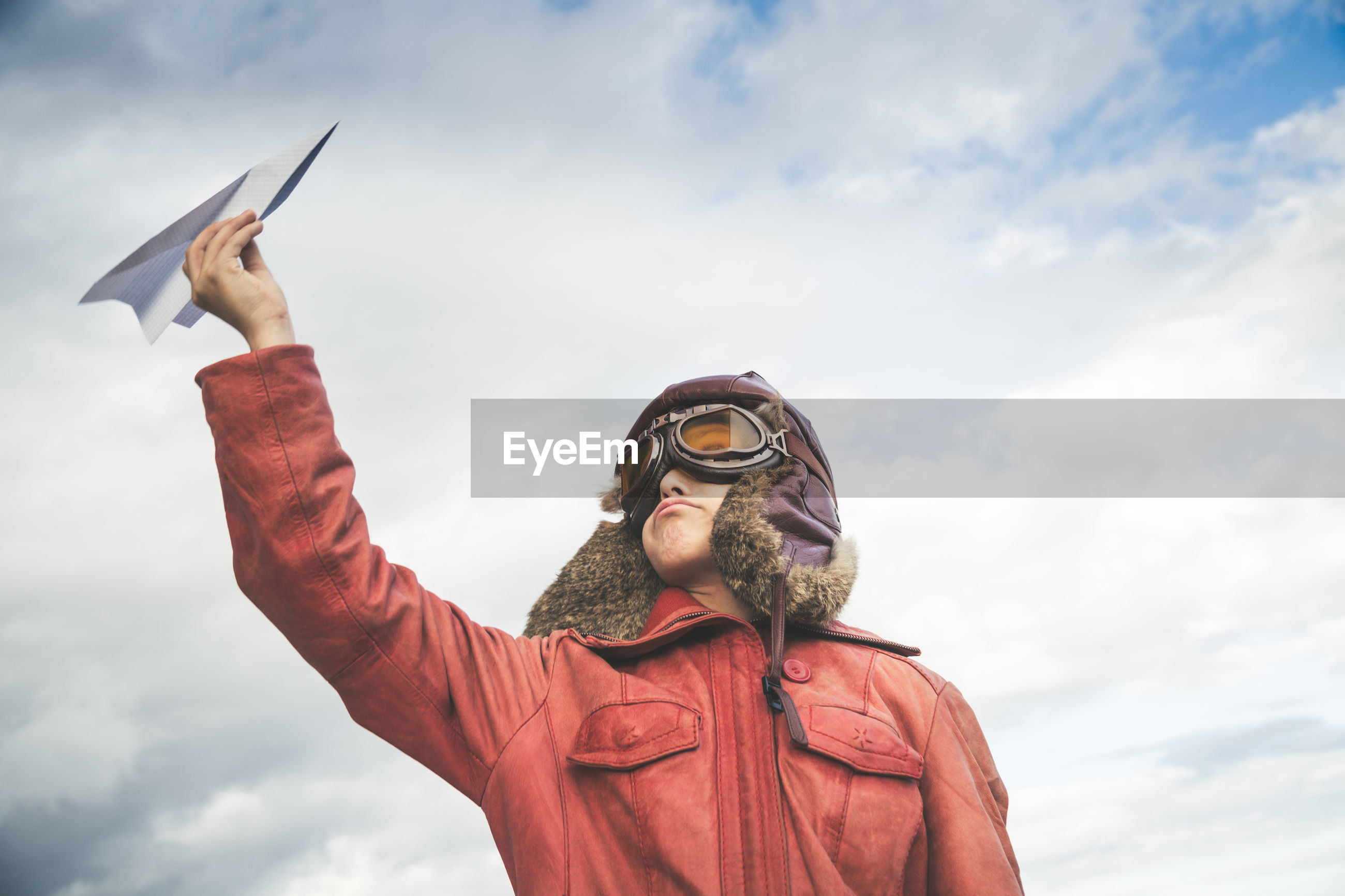Boy playing with paper airplane against cloudy sky