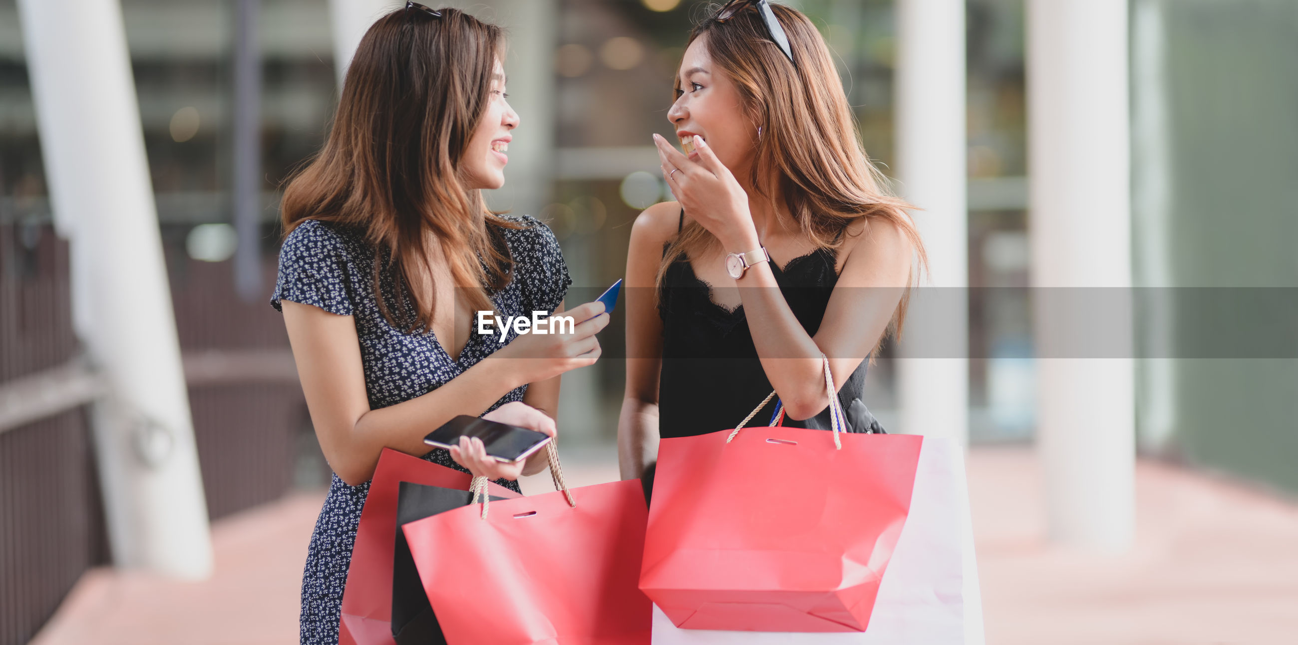 Cheerful friends with shopping bags walking in shopping mall