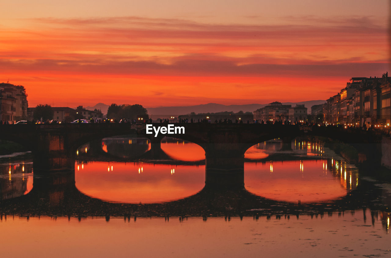Evening view to arno river with bridges and reflections in florence, italy