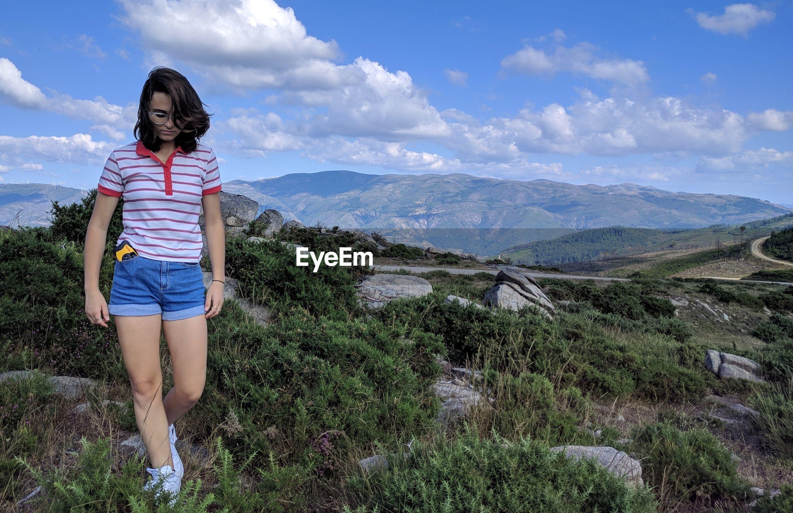 Teenage girl walking on field against sky