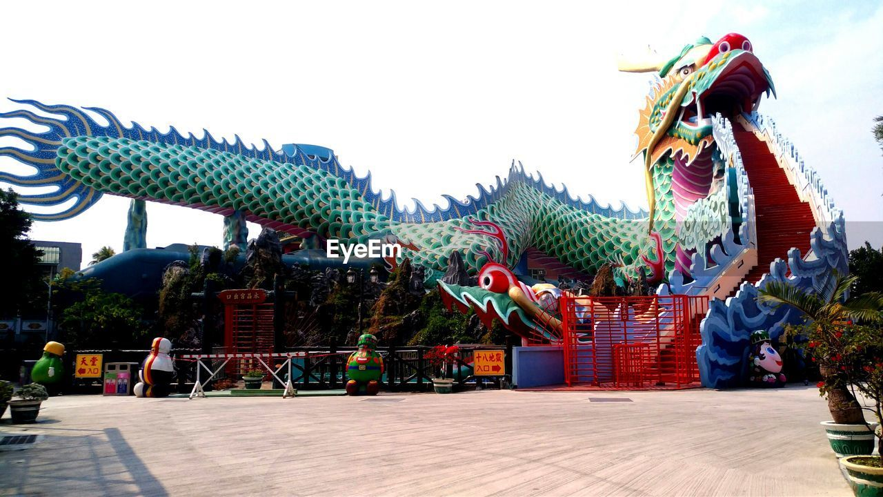 outdoors, dragon, day, built structure, sky, architecture, real people, statue, building exterior, clear sky, chinese dragon, nature
