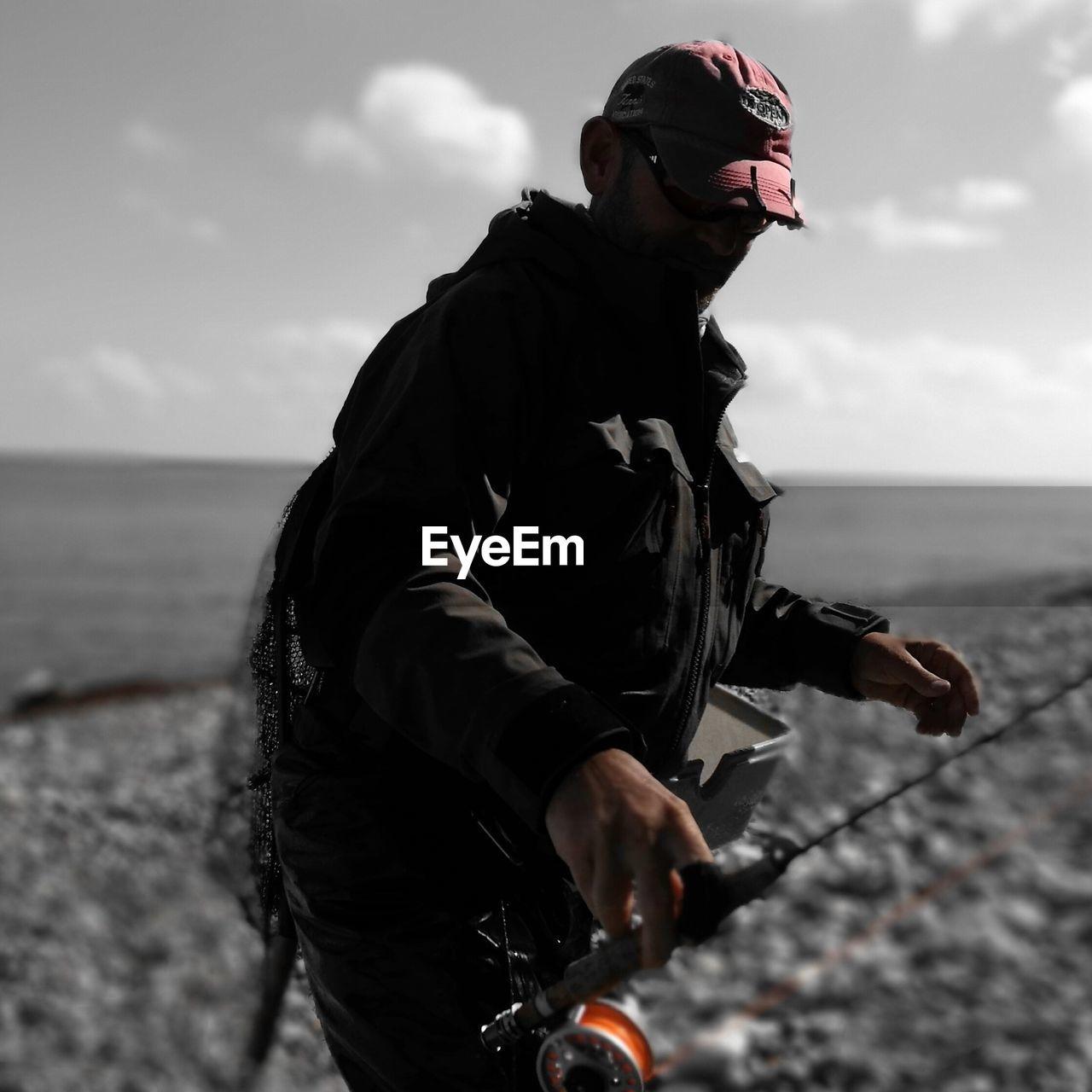 Man holding fishing rod at beach