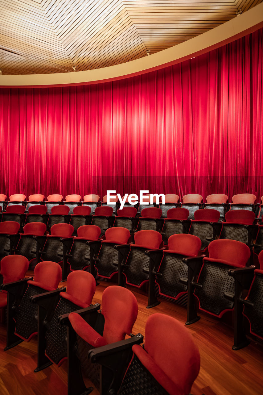 seat, chair, empty, arts culture and entertainment, indoors, red, movie theater, absence, stage, stage - performance space, stage theater, curtain, no people, in a row, performance, auditorium, illuminated, spotlight, event, theatrical performance, nightlife, luxury
