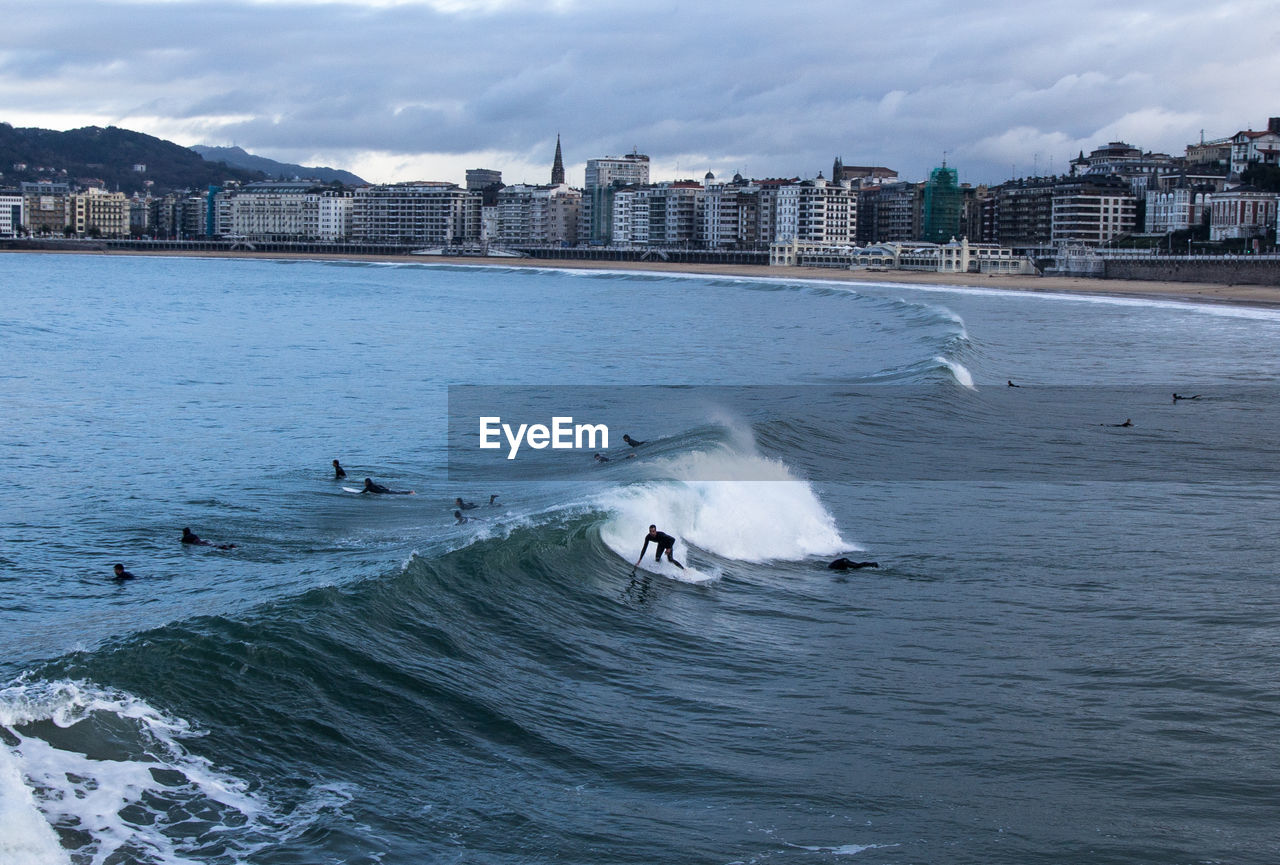 water, building exterior, sea, architecture, built structure, motion, waterfront, city, sky, wave, nature, sport, cloud - sky, beauty in nature, day, aquatic sport, outdoors, scenics - nature, vertebrate, cityscape