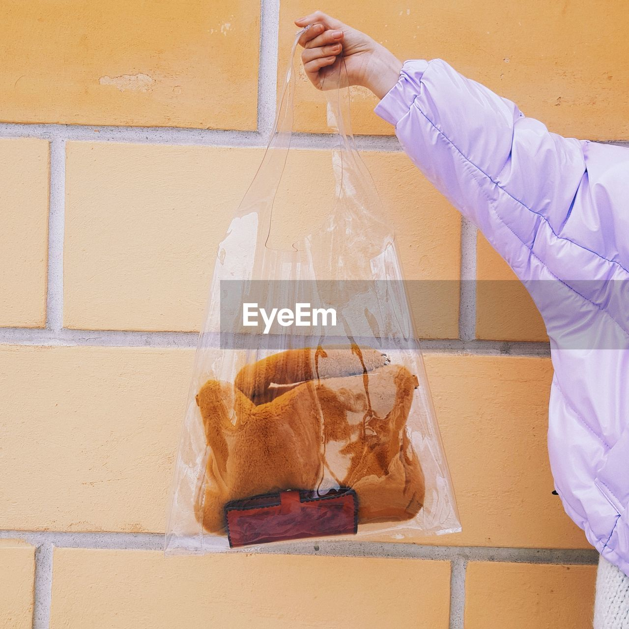 Cropped hand of woman holding warm clothing with purse in plastic bag against orange wall