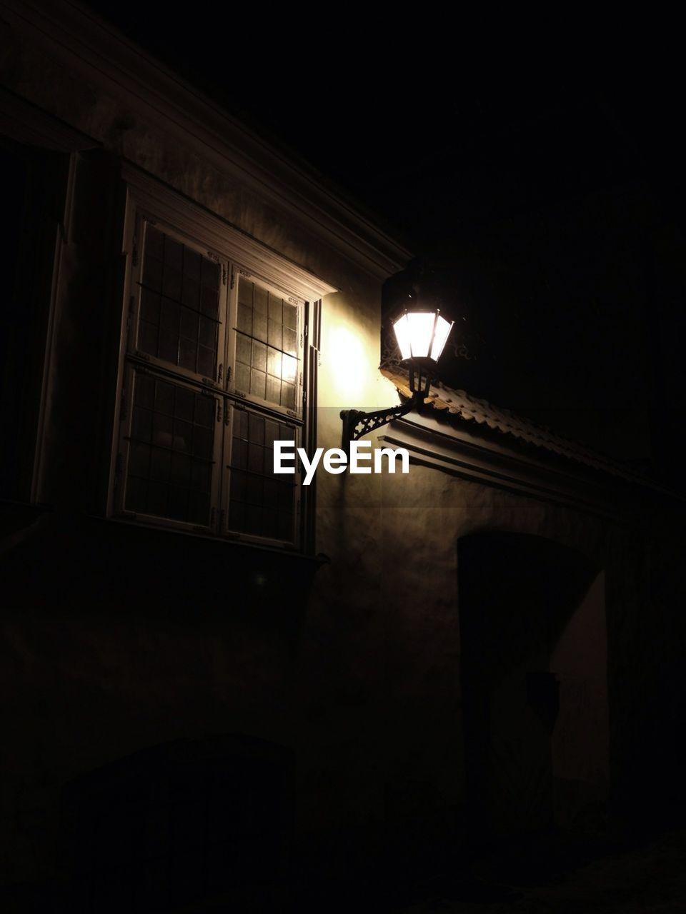 Illuminated electric lamp on house at night