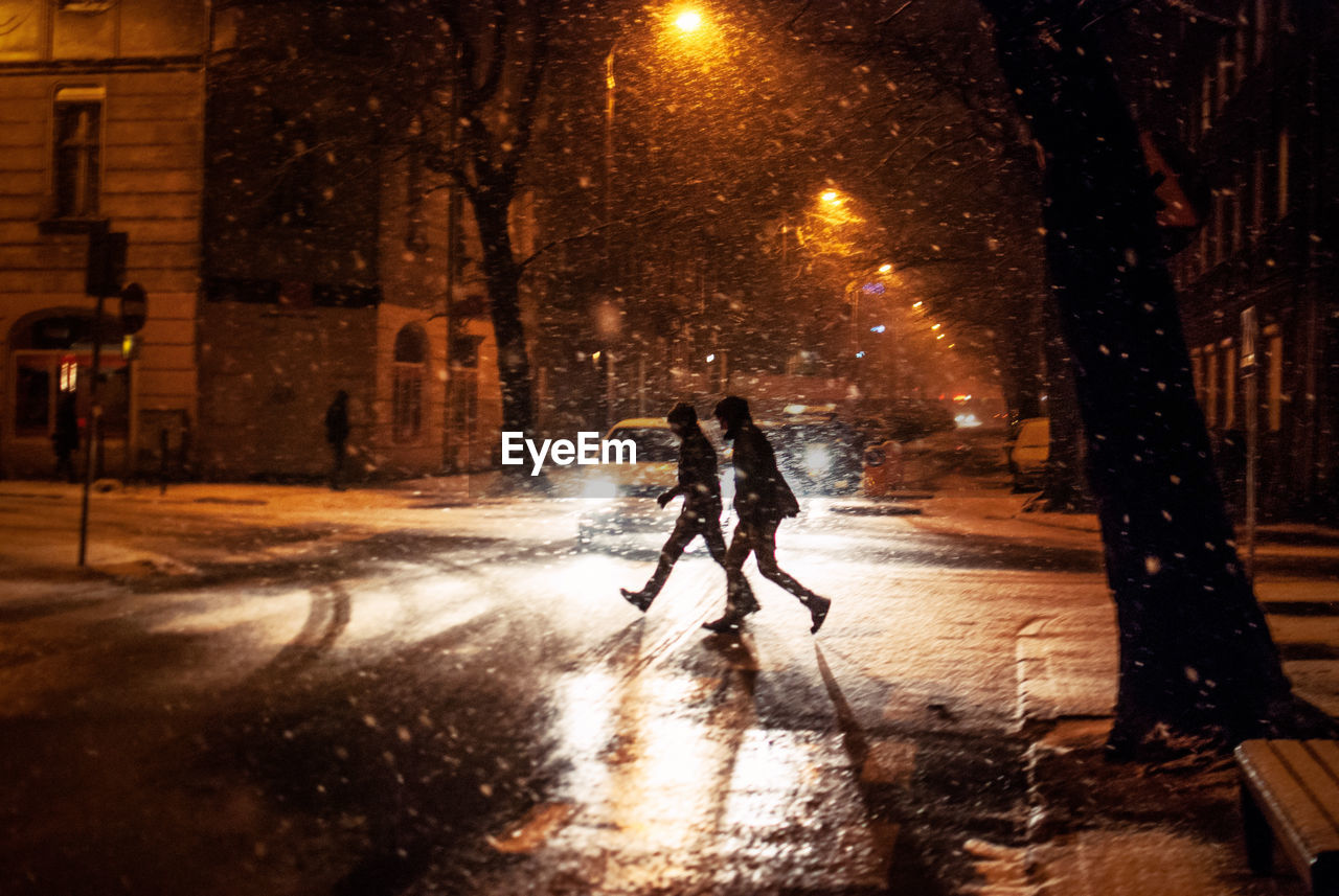 People Crossing Road During Snowfall In City At Night