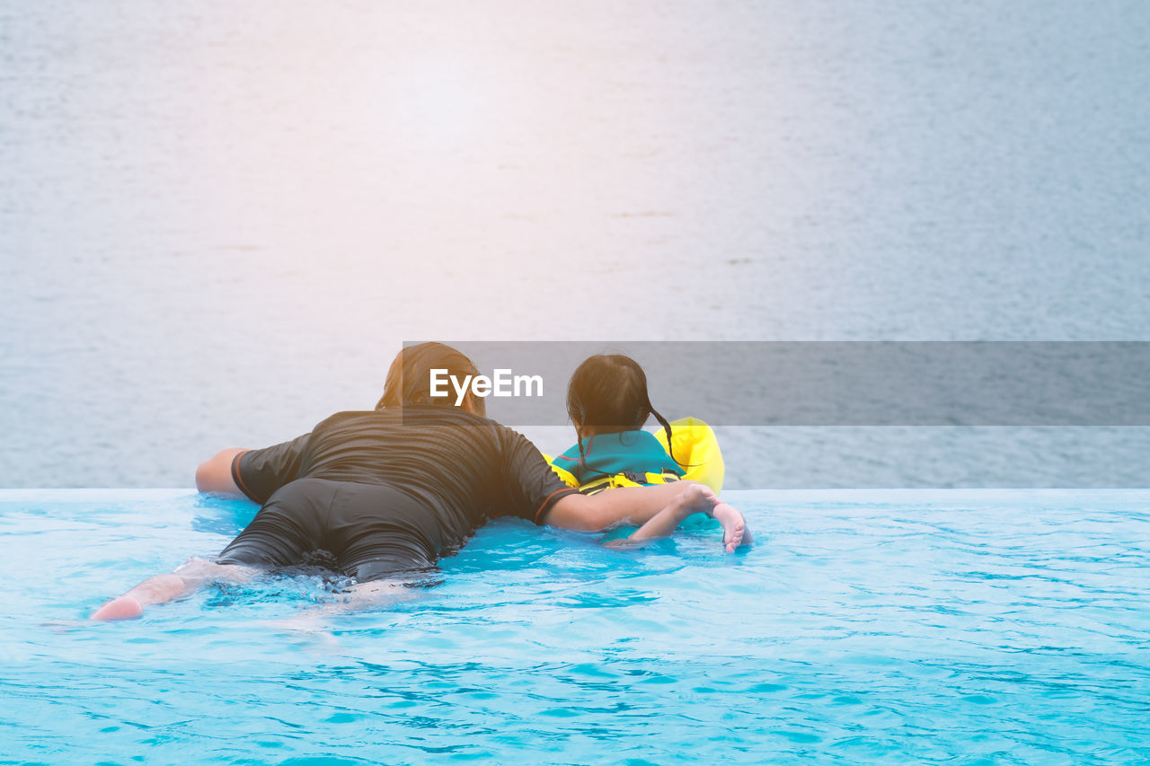 Rear view of man with daughter looking at sea while swimming in infinity pool