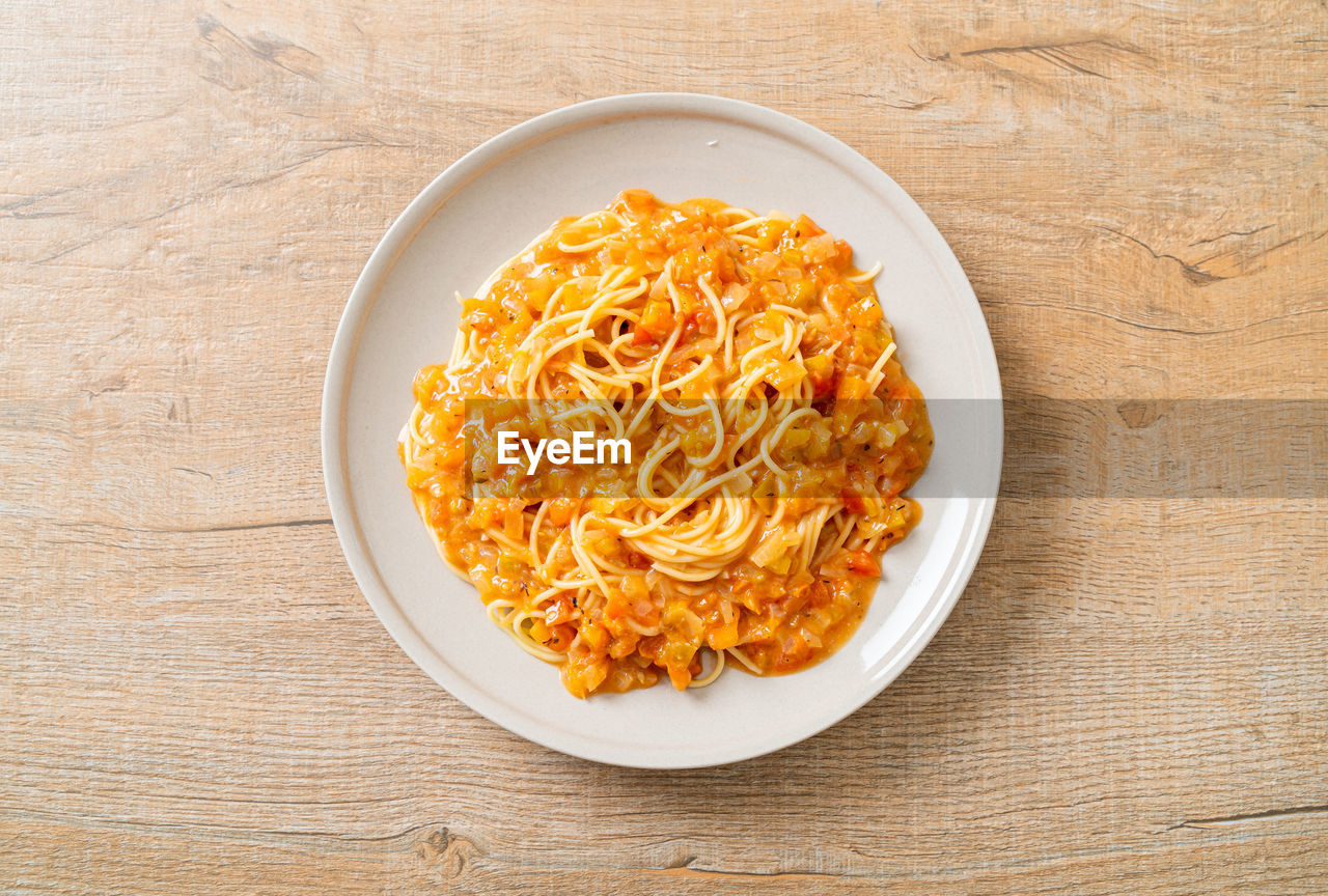 HIGH ANGLE VIEW OF PASTA IN BOWL ON TABLE AGAINST WALL
