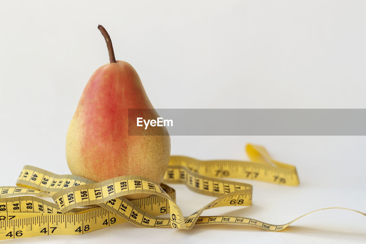 healthy eating, still life, fruit, food and drink, food, close-up, wellbeing, indoors, no people, studio shot, freshness, white background, pear, yellow, copy space, group of objects, focus on foreground, tape measure, selective focus, table, ripe