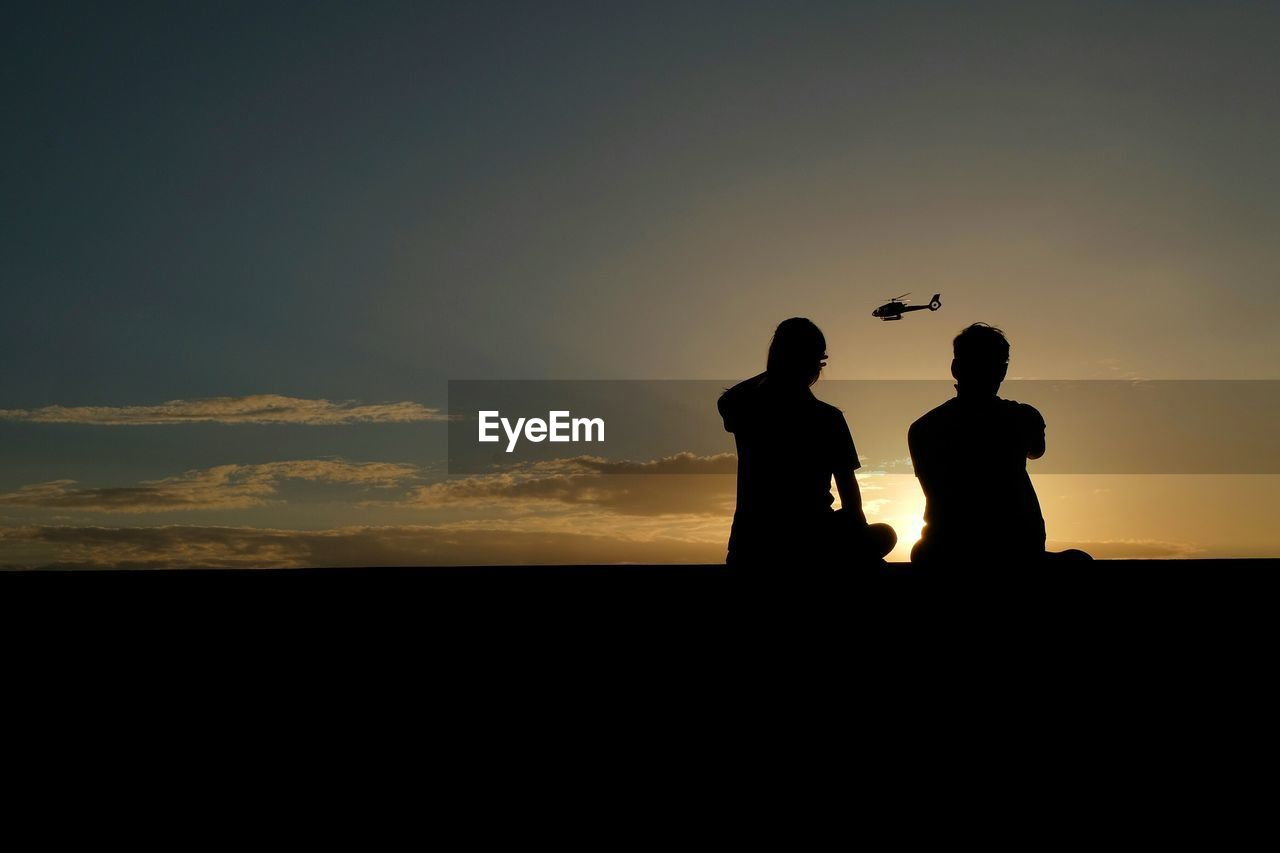 Silhouette People And Helicopter Against Sky During Sunset
