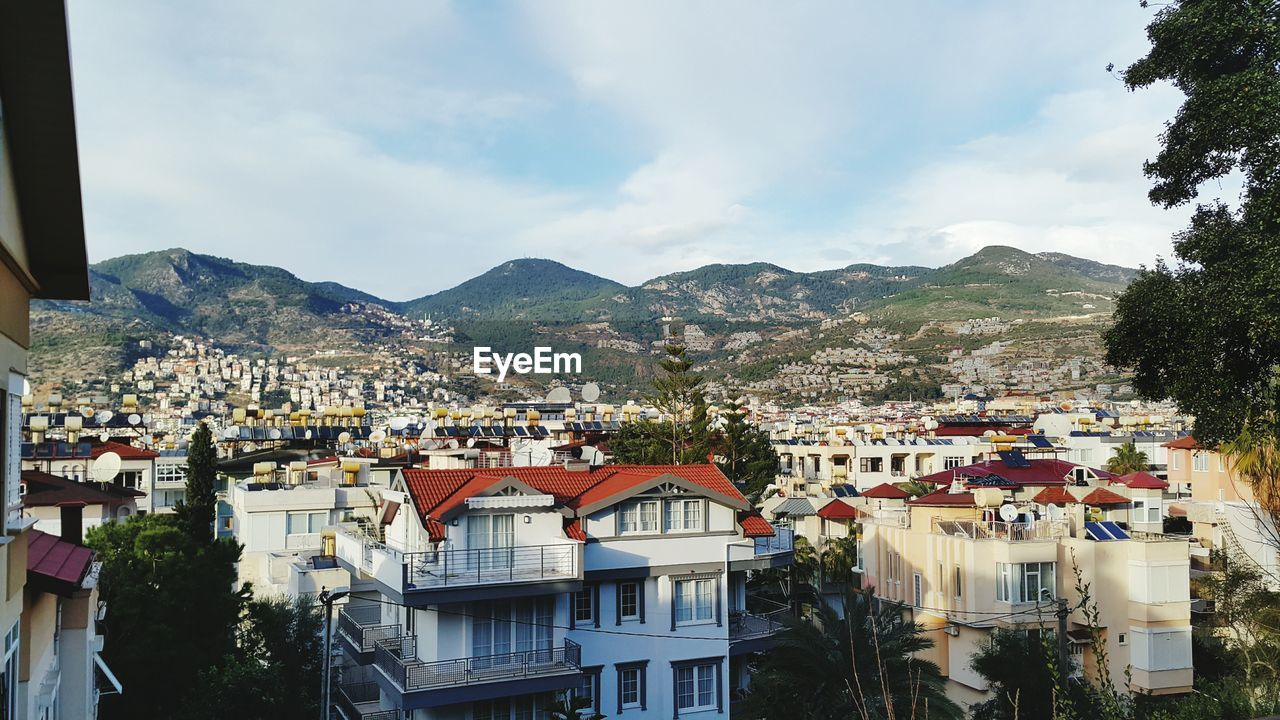 building exterior, architecture, built structure, mountain, building, residential district, sky, city, cloud - sky, nature, no people, day, house, tree, plant, town, outdoors, mountain range, high angle view, community, cityscape, townscape, row house, apartment