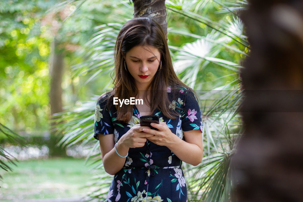 Young woman using mobile phone while standing against tree