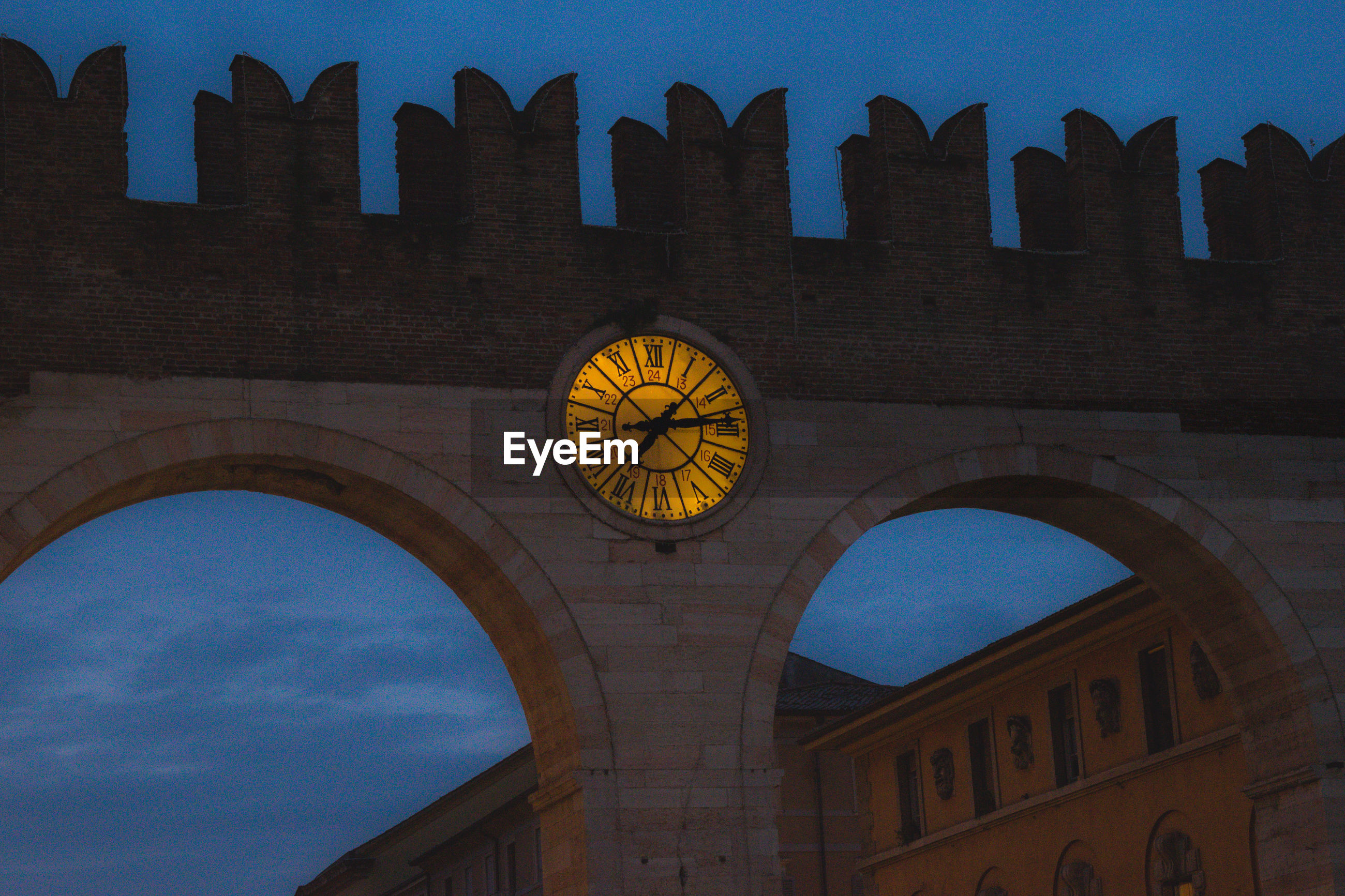 Low angle view of illuminated clock amidst arches at dusk